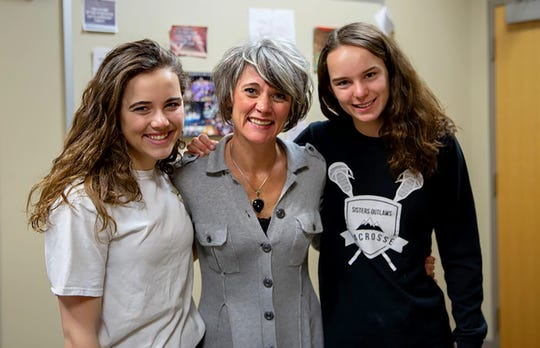 """Sisters High School students Sydney and Skylar Wilkins stand with health teacher Heather Johnson (center). """"Our students are more stressed than they've ever been,"""" Johnson says."""