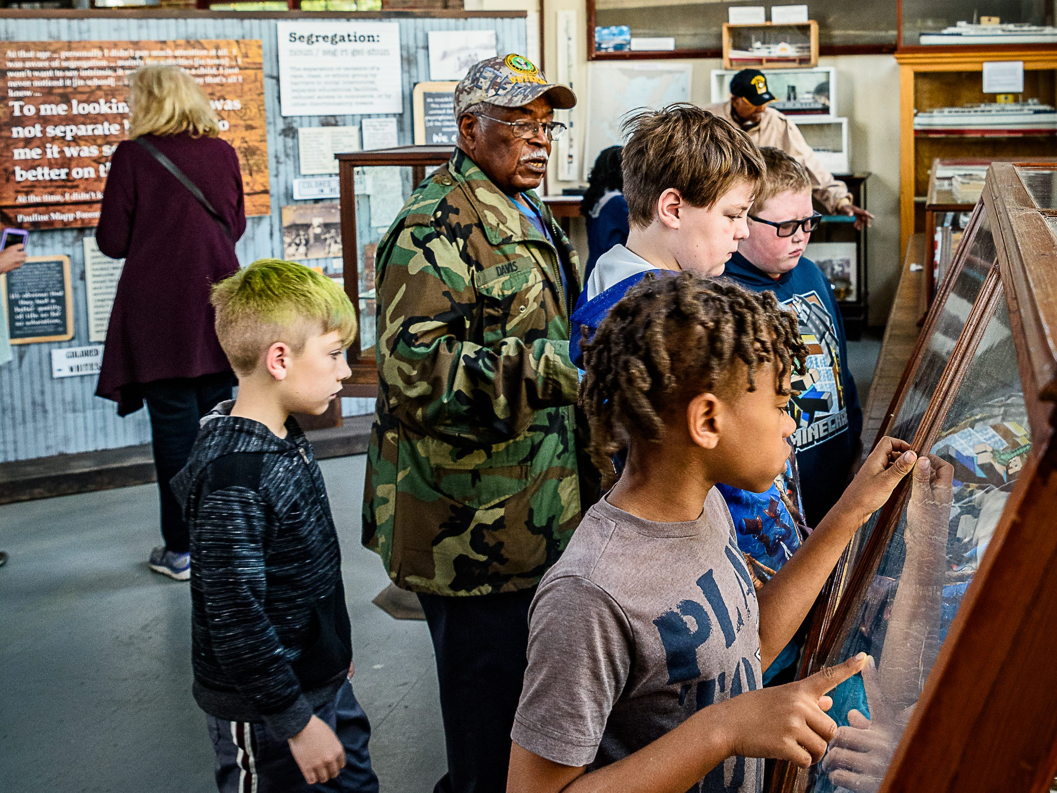 Former Rosenwald School student Bishop James Davis guides Kiptopeke fourth graders through the exhibits at the Cape Charles museum.