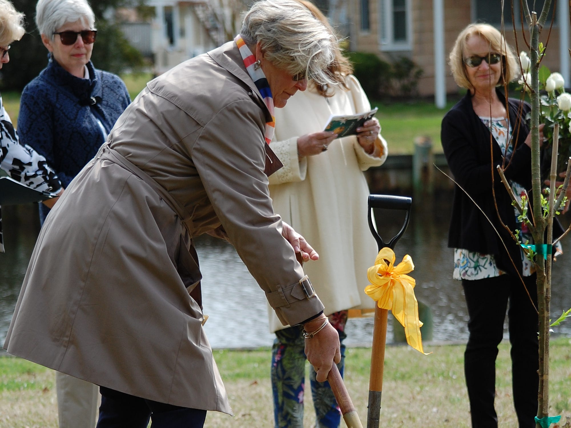Ocean Pines Garden Club President Linda Baker adds a shovel of soil to a newly planted tree in Pintail Park in memory of a loved one during the memorial ceremony on April 11.