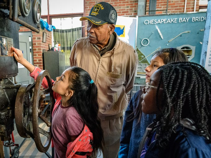 "Clarence Smaw, a former student of the Rosenwald school in Northampton County, helps the fourth graders from Kiptopeke Elementary School discover the generator that used to provide Cape Charles electric power at the Cape Charles Museum and Welcome Center. The students toured the various exhibits at the museum including the ""Building a Community: The Cape Charles Elementary (Rosenwald) School."""