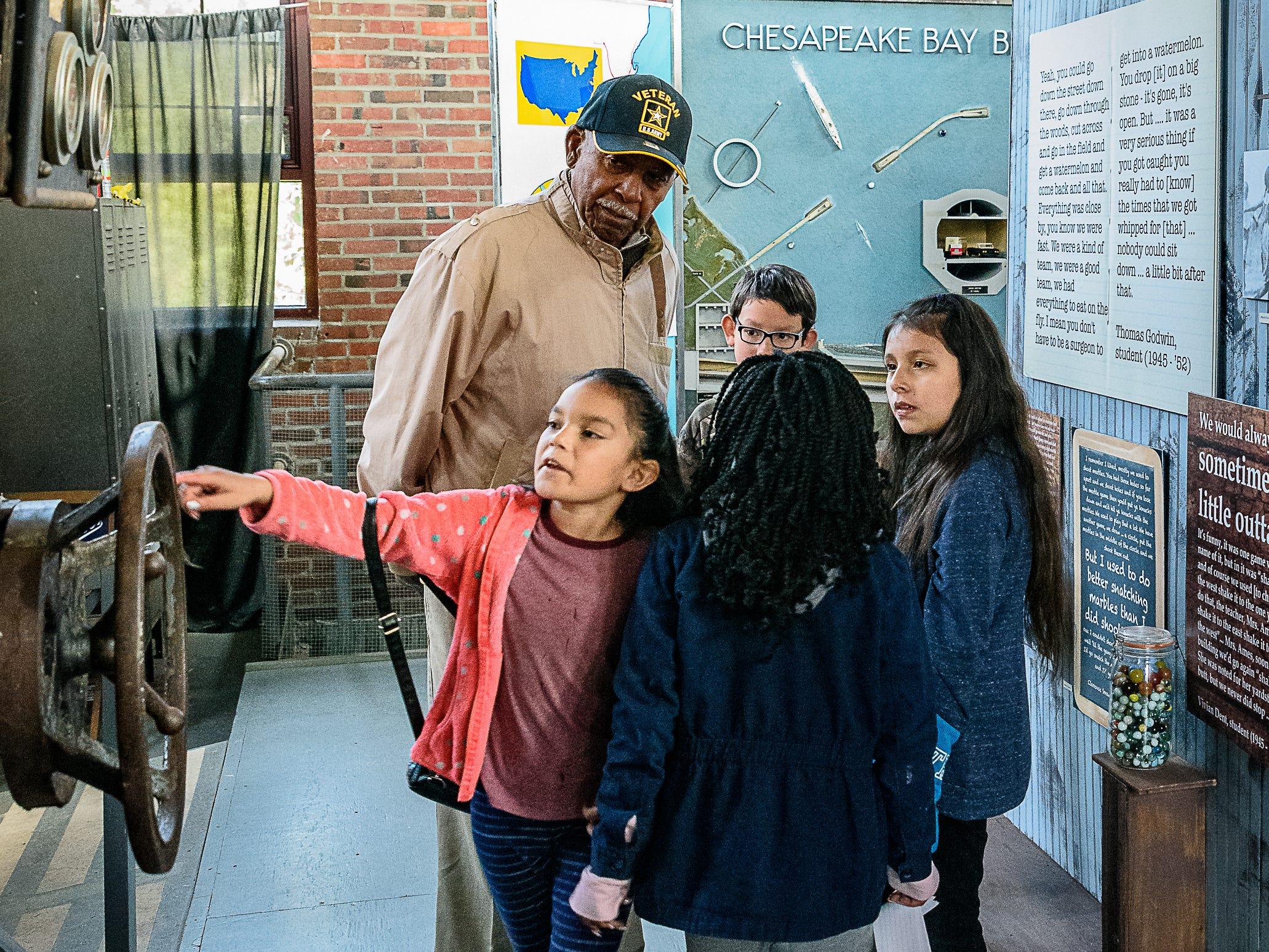 A student checks out an exhibit at the Cape Charles museum as Clarence Smaw, a former Rosenwald student, and other  Kiptopeke 4th graders look on.
