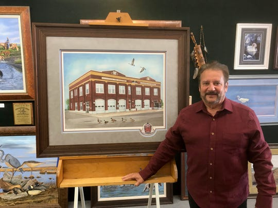 Kevin McBride stands beside his painting of the old Chincoteague firehouse in his Osprey Nest Art Gallery in Chincoteague, Virginia on Wednesday, April 10, 2019.