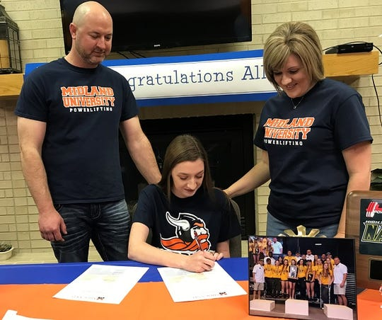 Calvary's Allie Lazarus signs a powerlifting scholarship to Midland University Thursday afternoon at the school.