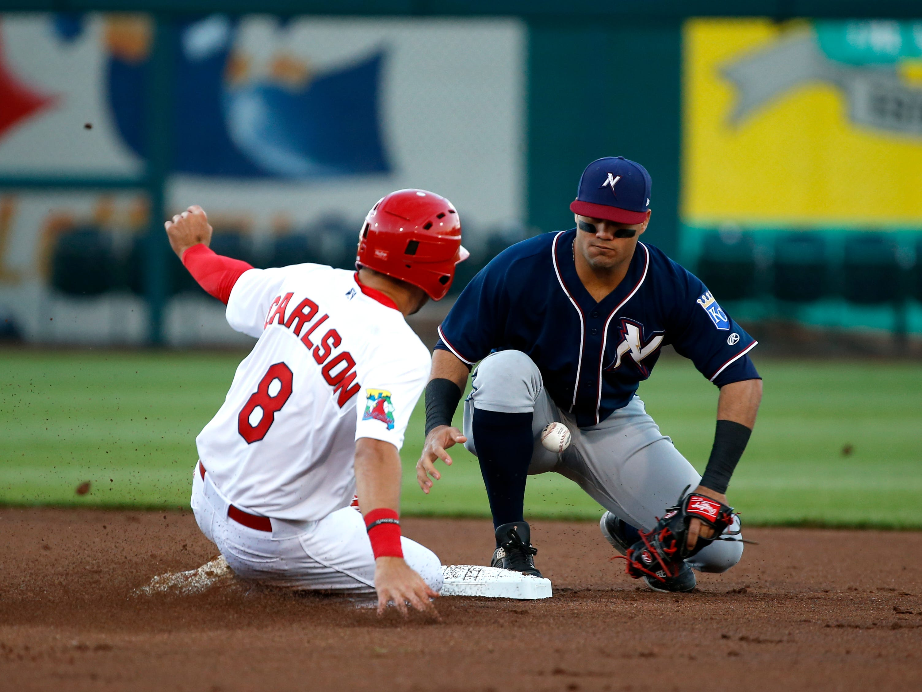 Springfield Cardinal Dylan Carlson slides safely into second as Northwest Arkansas Naturals second baseman Gabriel Cancel misses a throw at Hammons Field on Thursday, April 11, 2019 during the Cardinals home opener.