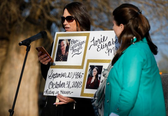 Amber May, left, holds a sign with pictures of her sister Torie May as she speaks during the Victims Memorial Garden Brick Dedication on Thursday, April 11, 2019.