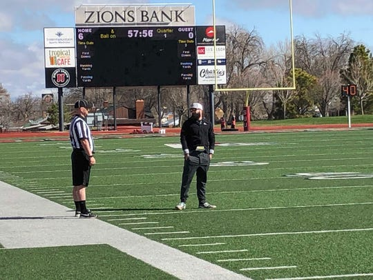 New SUU defensive coordinator Brandon Fisher talks with a practice referee during the T-Birds' spring practice.