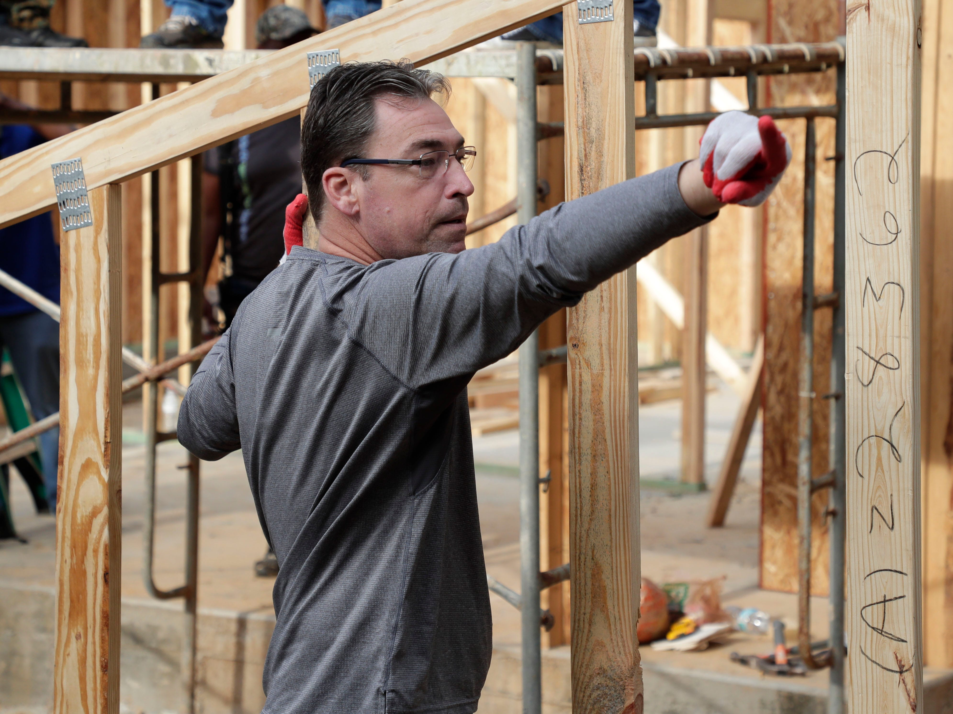 Chief of Police Michael DeLeo assists in lifting a frame for the roof of the future home for Recha Evans and her family Friday, April 12, 2019. Elected and appointed city officials, employee volunteers and representatives from Habitat for Humanity work together to build Evans' home.