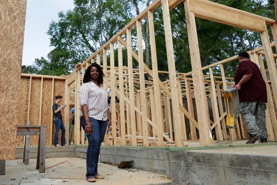 Recha Evans stands inside her future home as elected and appointed city officials, employee volunteers and representatives from Habitat for Humanity work to build Evans' home Friday, April 12, 2019.