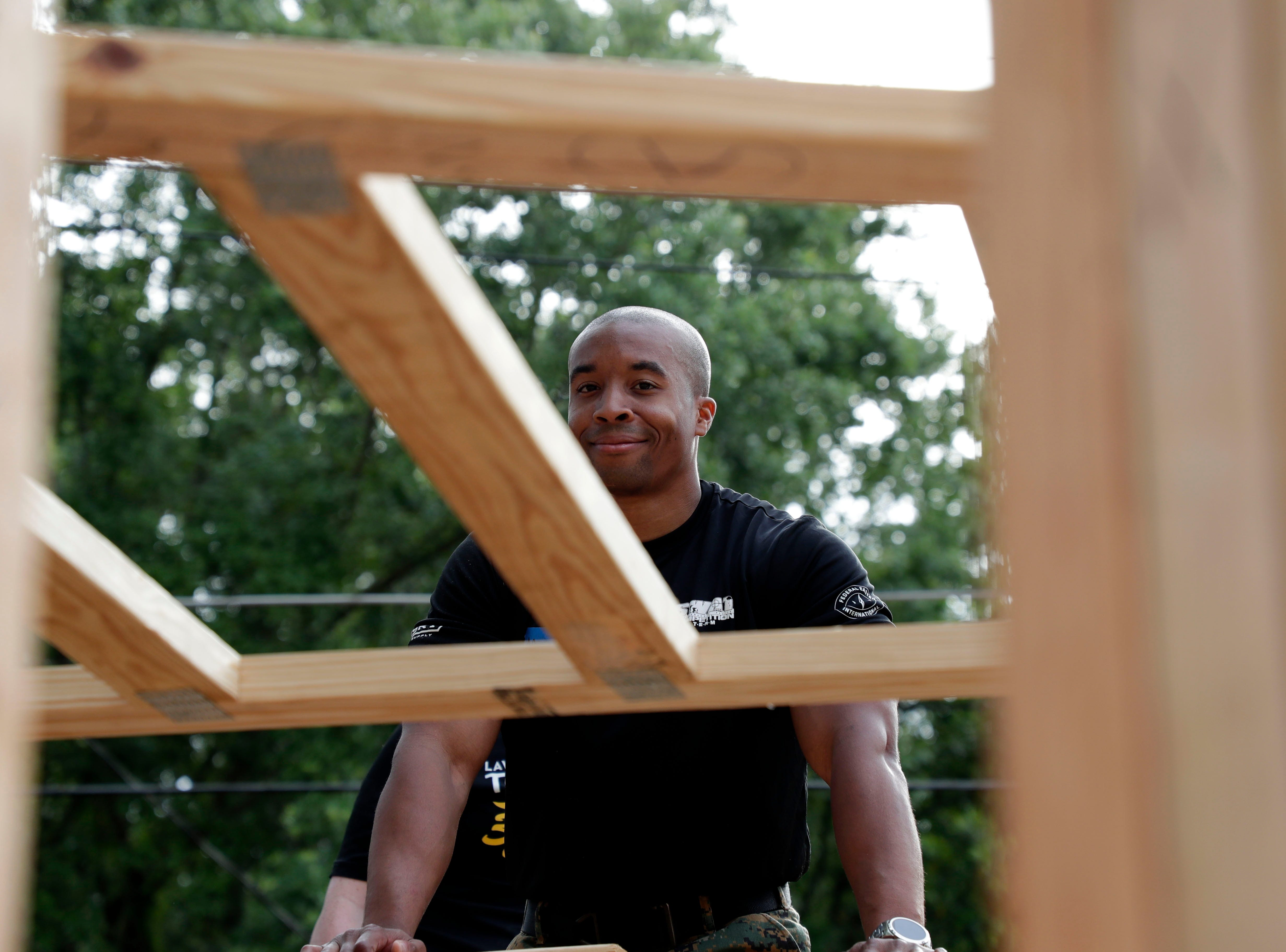 Marcus Johnson, an investigator with the Tallahassee Police Department smiles as he works alongside elected and appointed city officials, employee volunteers and representatives from Habitat for Humanity Friday, April 12, 2019. Together the volunteers are working to build the future home for Recha Evans and her children.