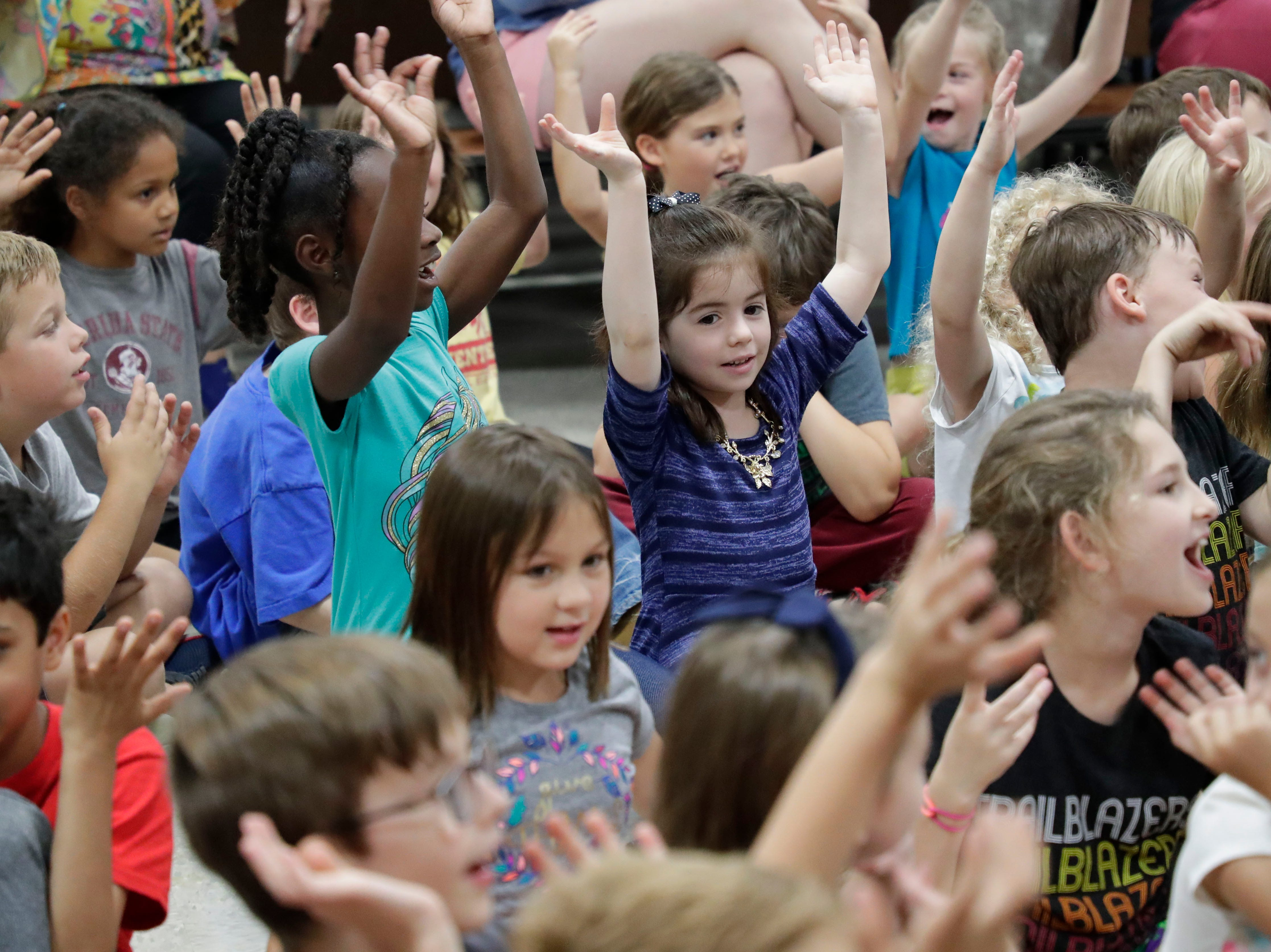 """Students at DeSoto Trail Elementary School wave their hands in the air as the author of the original """"Pete the Cat,"""" Eric Litwin, sings a tune Friday, April 12, 2019."""