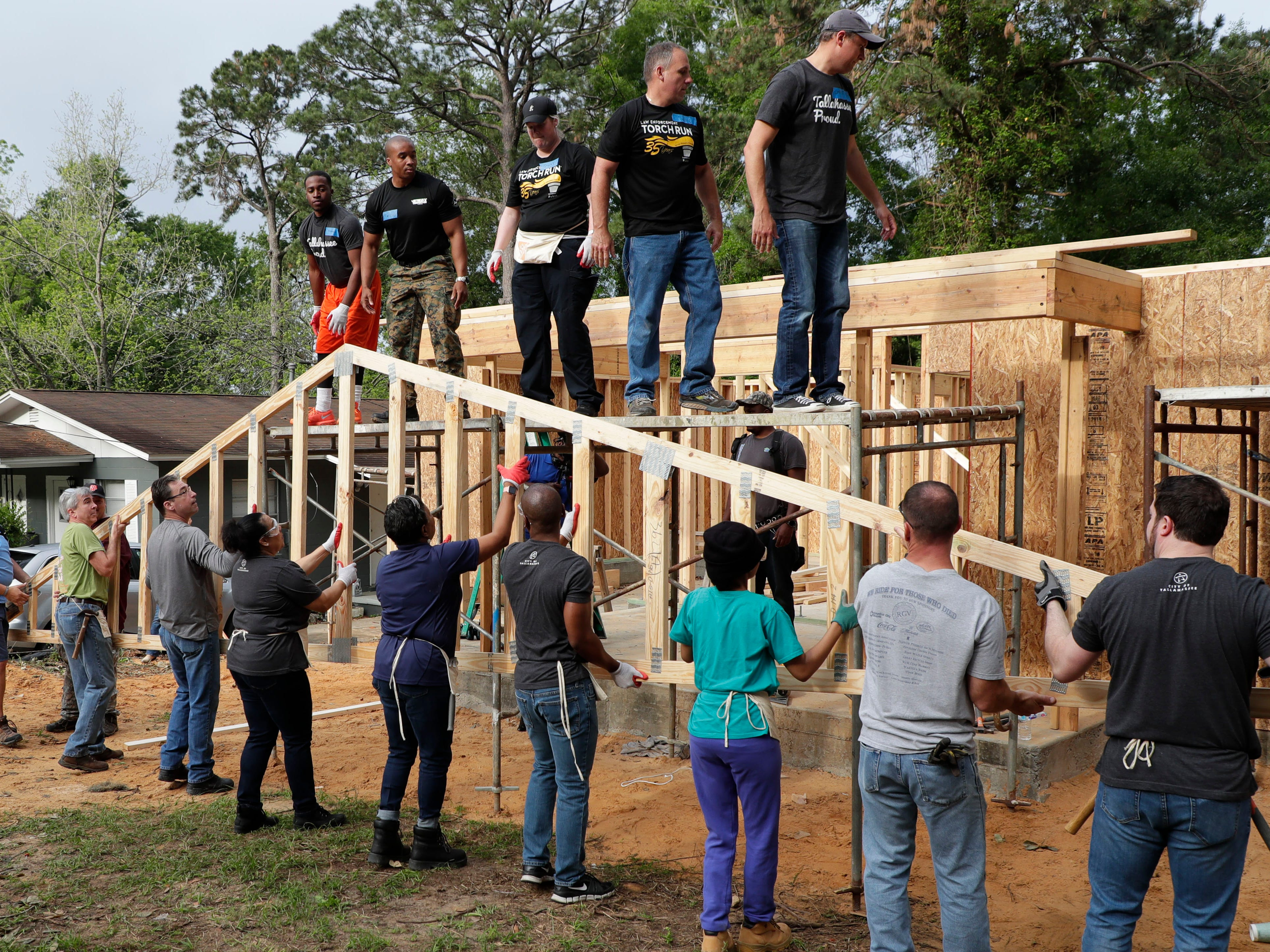 Elected and appointed city officials, employee volunteers and representatives from Habitat for Humanity work together to build a home for Recha Evans and her family Friday, April 12, 2019.