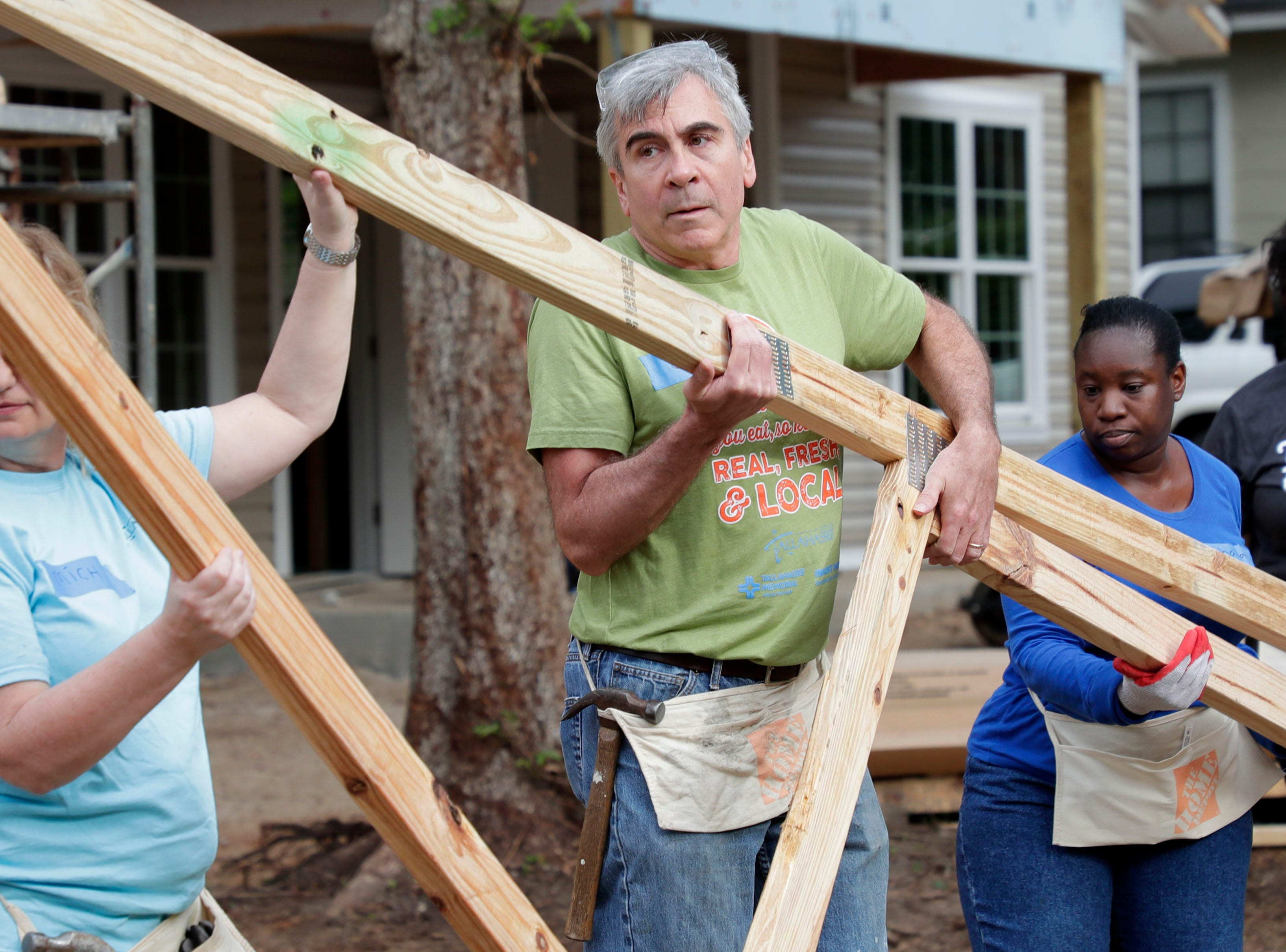Treasurer-Clerk Jim Cooke along with other volunteers move the framework for the roof of the future home for Recha Evans and her family Friday, April 12, 2019. Elected and appointed city officials, employee volunteers and representatives from Habitat for Humanity work together to build Evans' home.