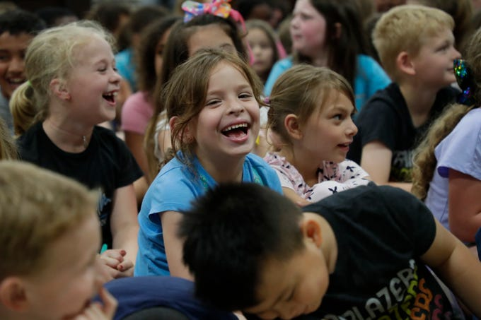 """A student at DeSoto Trail Elementary School giggles with her classmates as Eric Litwin, the author of the original """"Pete the Cat,"""" jokes with the students and teachers Friday, April 12, 2019."""