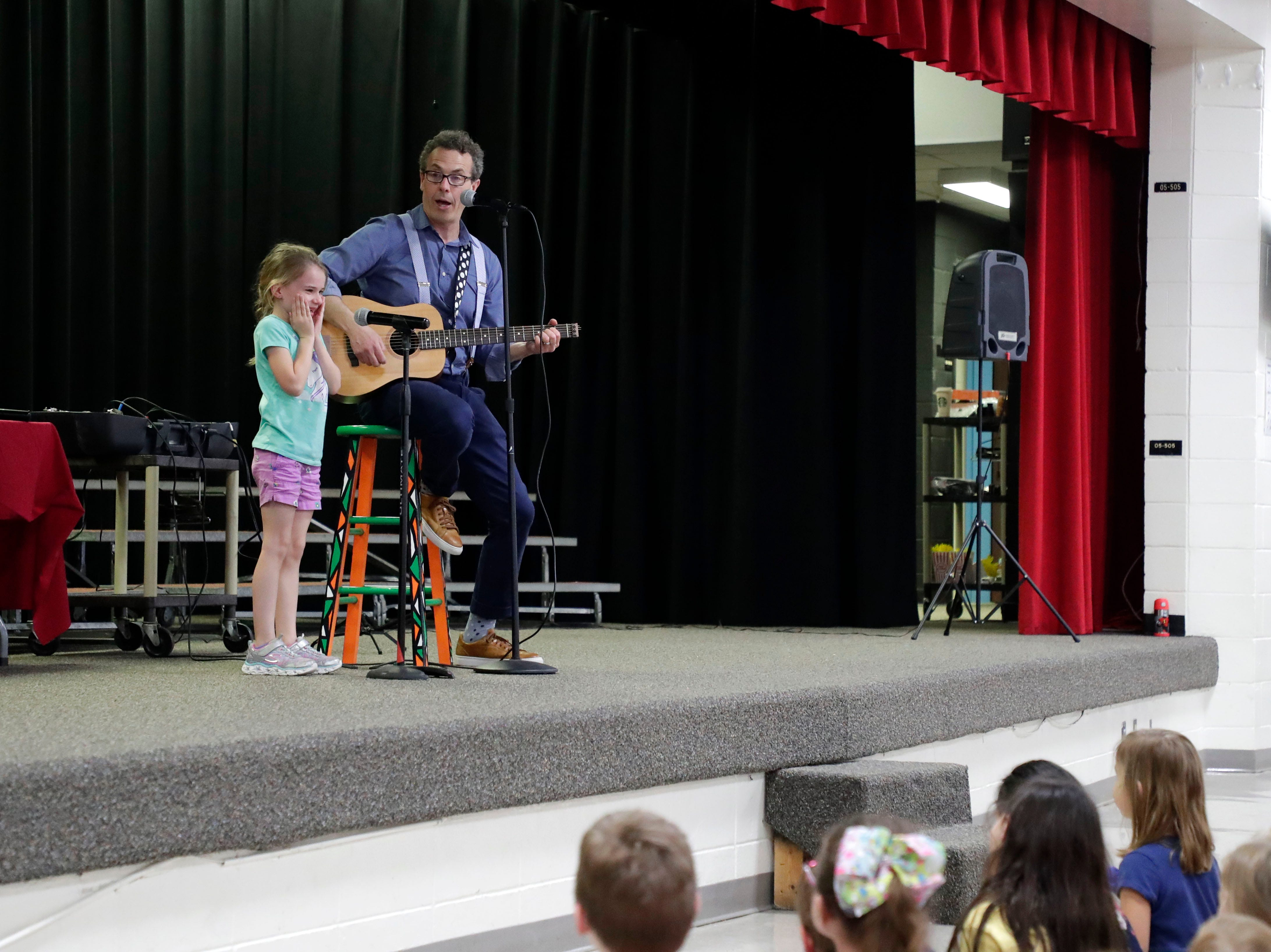 """Eric Litwin, author of the original """"Pete the Cat,"""" right, sings a song with DeSoto Trail Elementary School student Riley Bergozza, 6, Friday, April 12, 2019."""