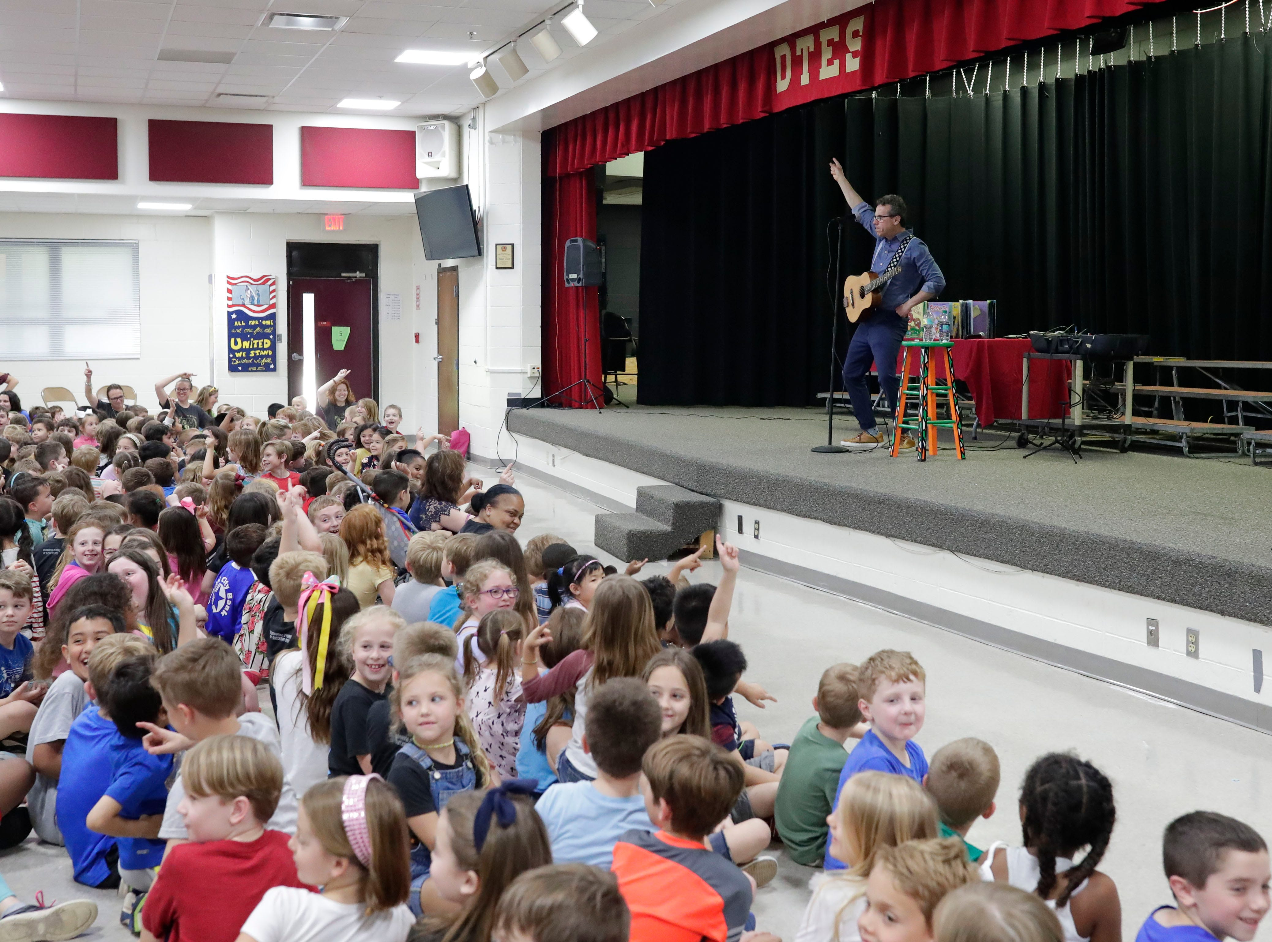 """Eric Litwin, author of the original """"Pete the Cat,"""" right, performs at DeSoto Trail Elementary School for a crowd of students Friday, April 12, 2019."""
