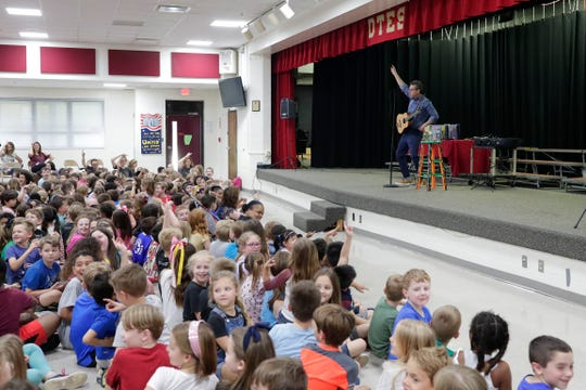 "Eric Litwin, author of the original ""Pete the Cat,"" right, performs at DeSoto Trail Elementary School for a crowd of students Friday, April 12, 2019."
