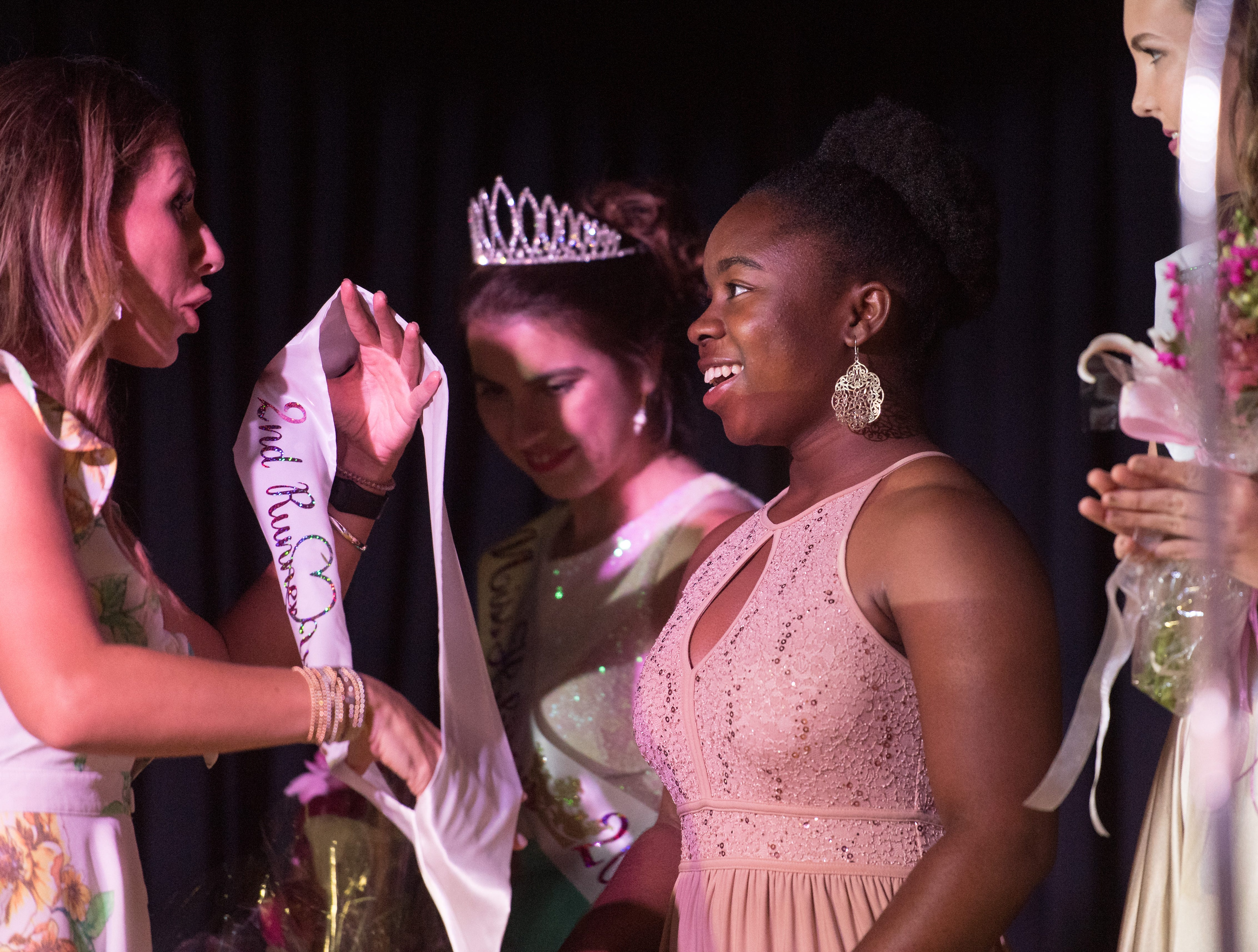The 2019 Miss Hibiscus Pageant second runner-up Unique Edden (center) is awarded onstage Thursday, April 11, 2019, at the Heritage Center in Vero Beach.