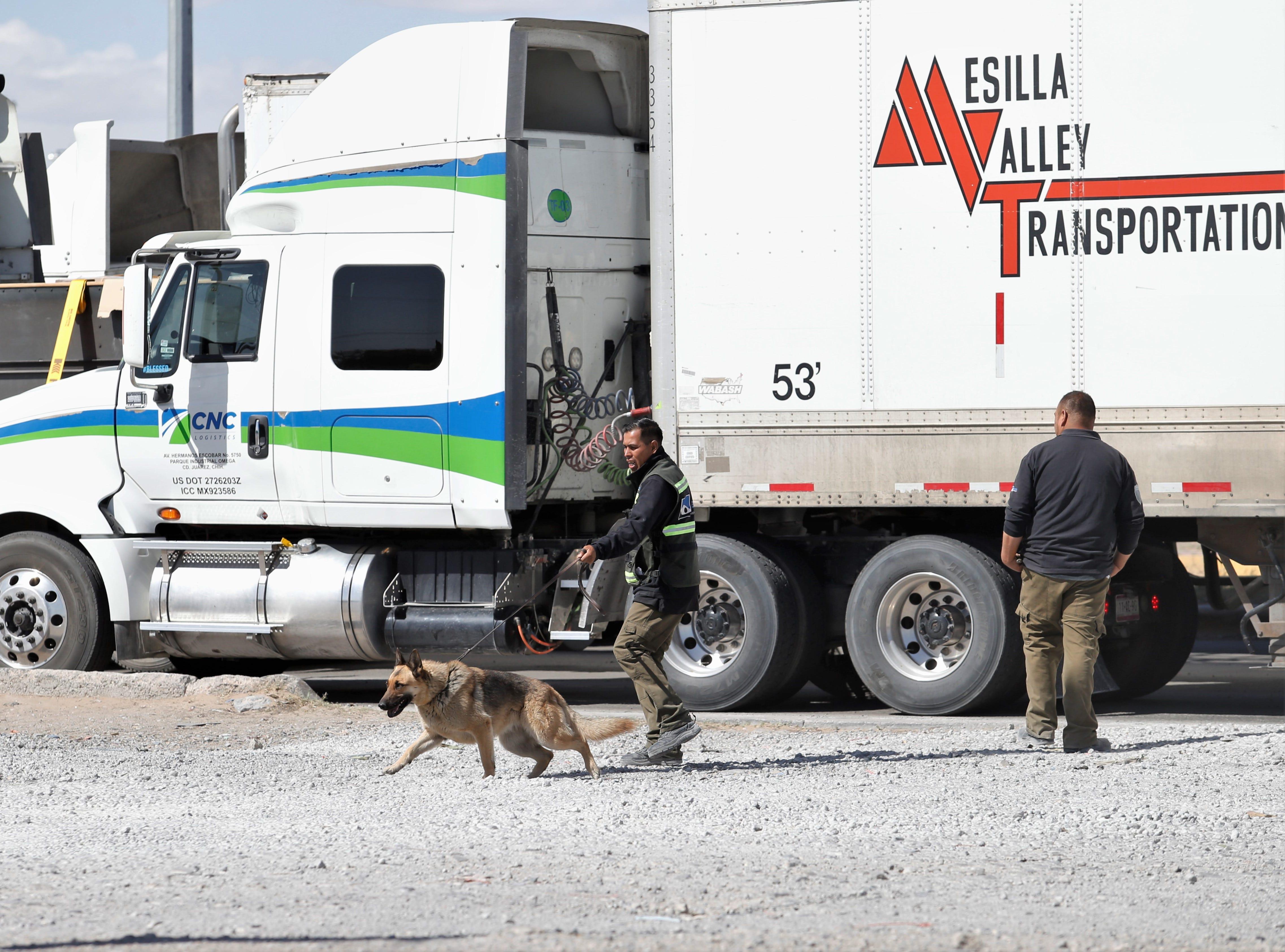 Security contractors inspect long lines of commercial trucks as they line Juarez's Juan Pablo II Boulevard.