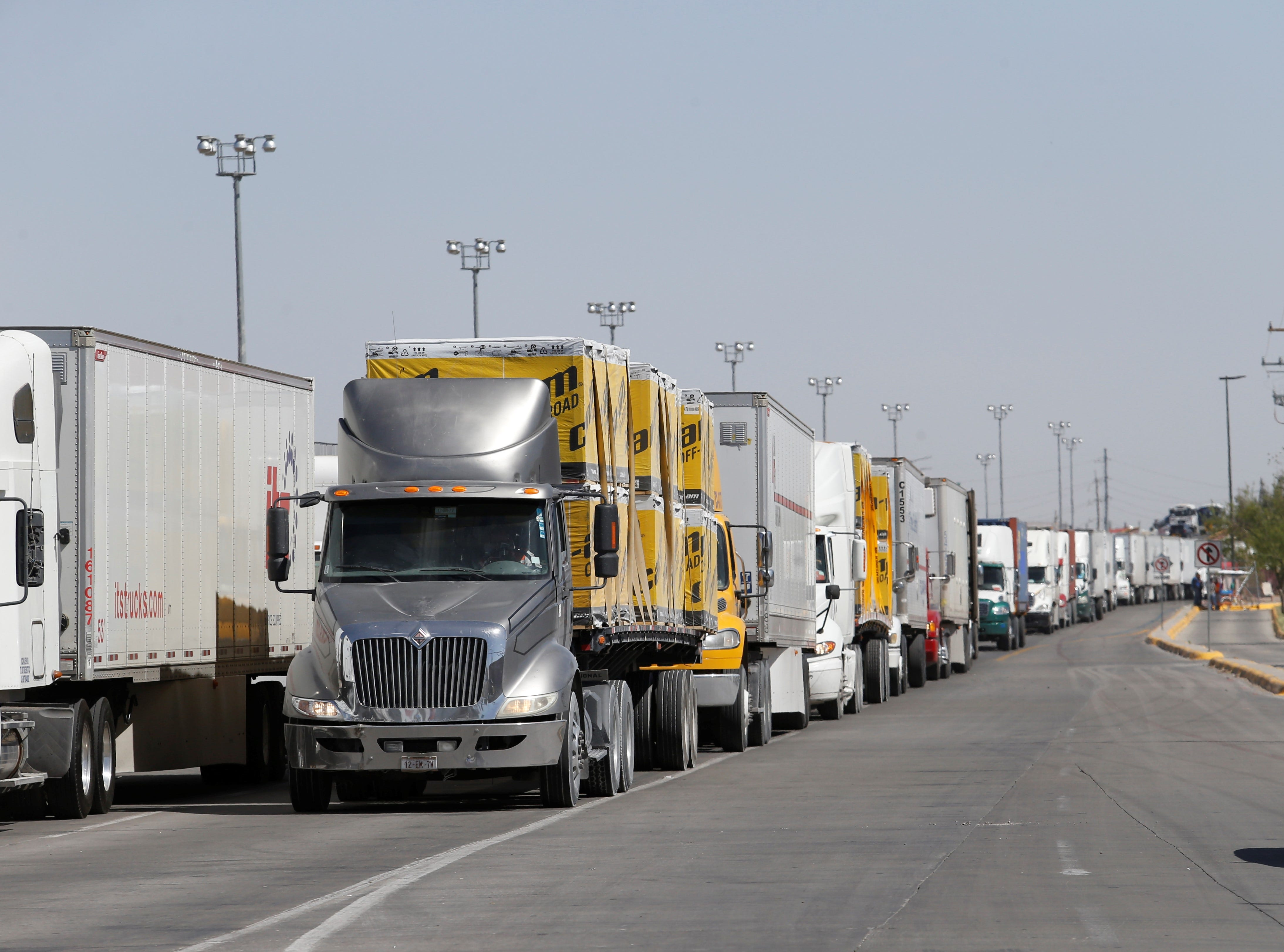 Long lines of commercial trucks line Juarez's Juan Pablo II Boulevard as they wait to cross the international Bridge of the Americas into the United States. Some drivers have waited a day to cross.
