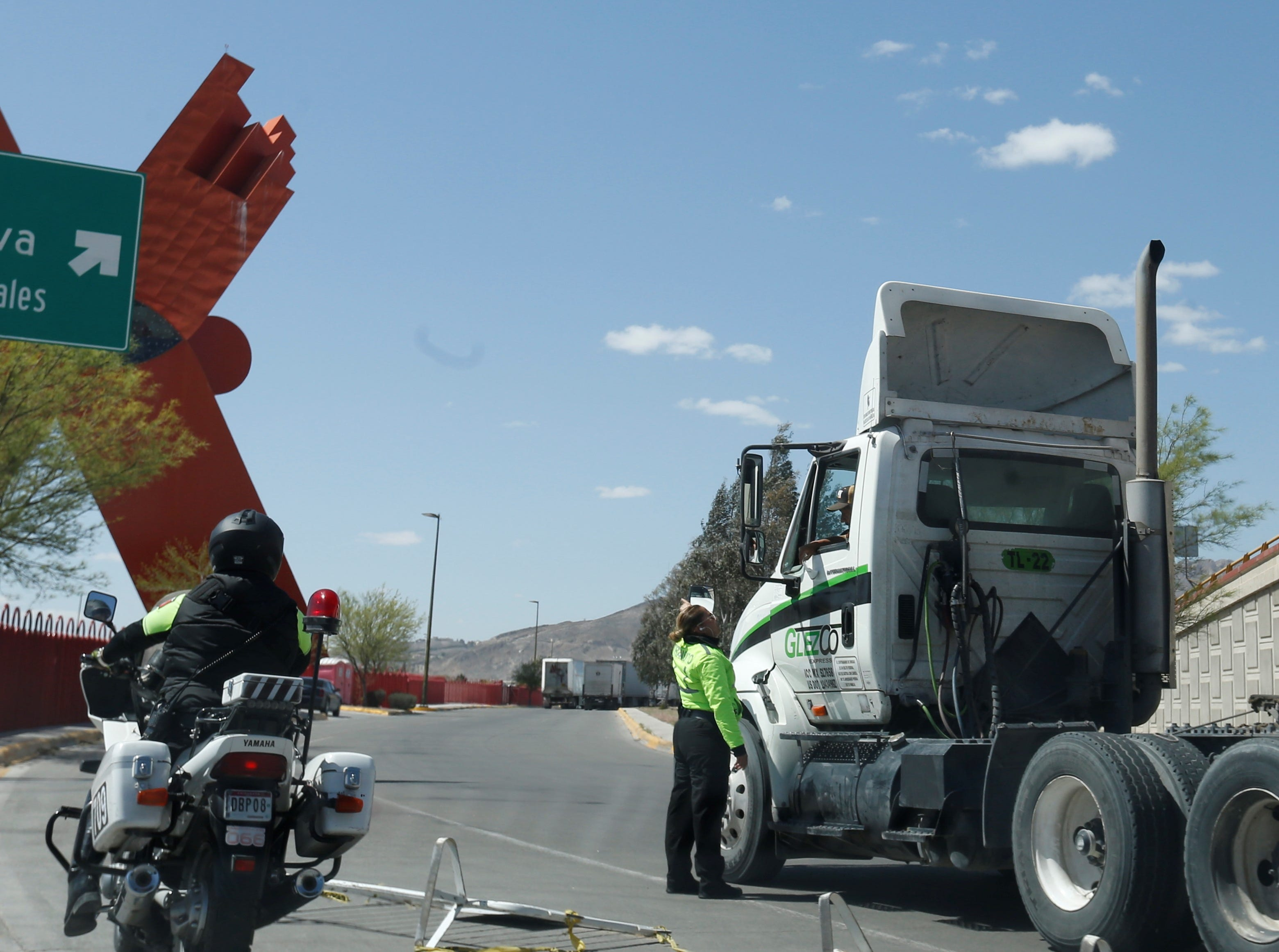 The city of Juarez's traffic police help direct long lines of commercial trucks on Juan Pablo II Boulevard as they wait to cross into the United States.