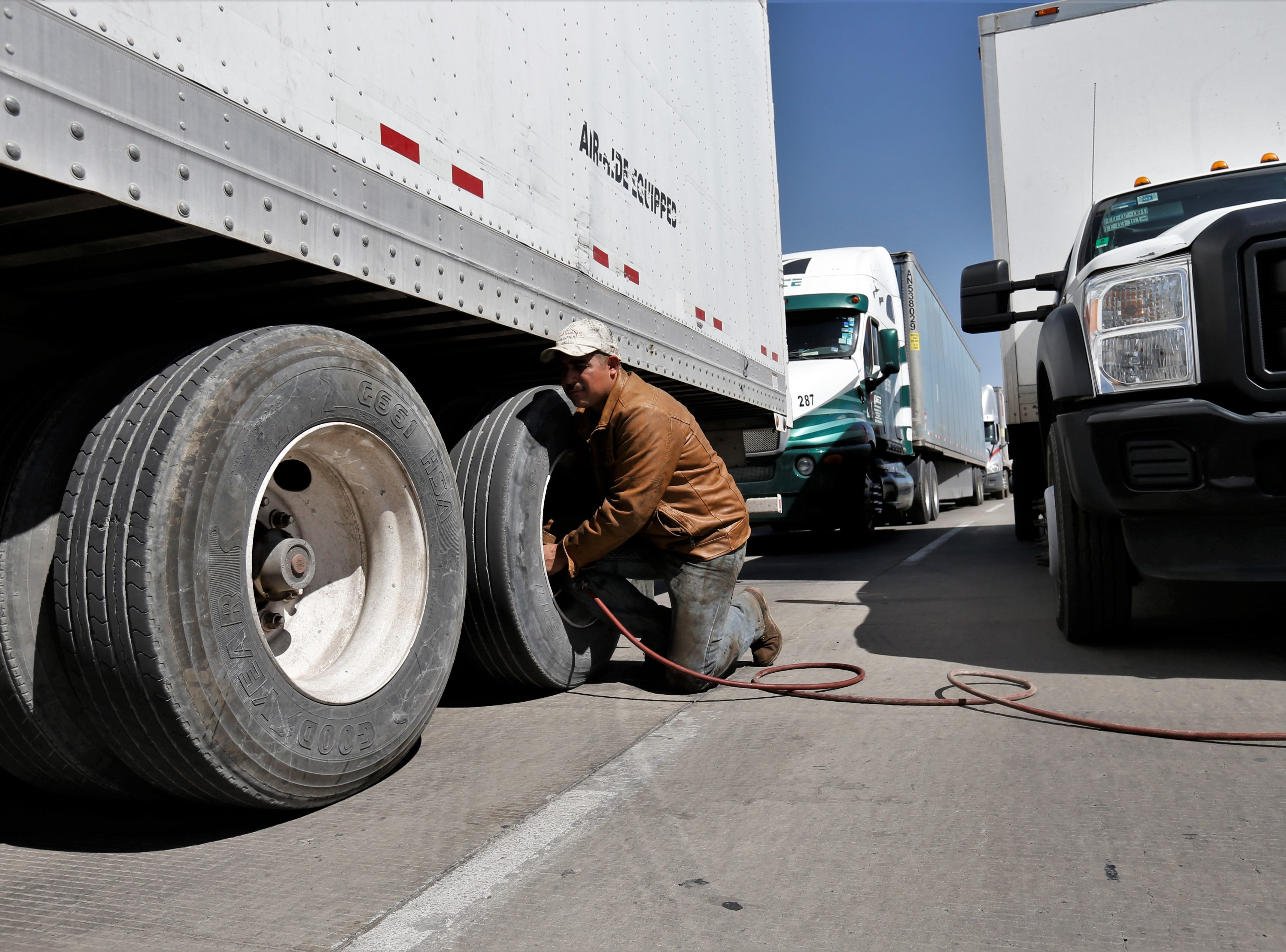 Juarez's CNC Logistics employee helps inflate wheels of commercial trucks waiting to cross the international Bridge of the Americas.