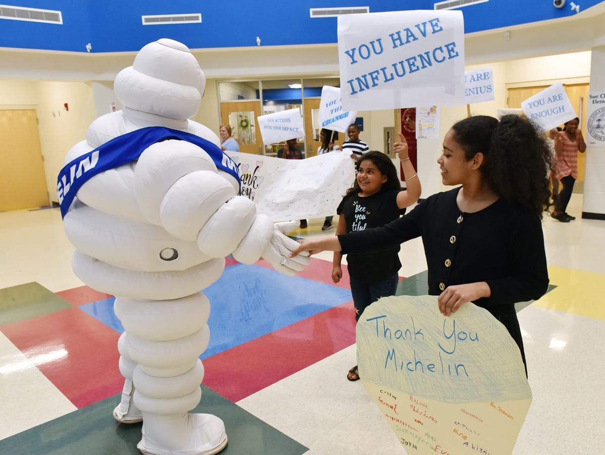 Sue Cleveland Elementary School students greet the Michelin Man during the Michelin Challenge Education 10th Anniversary Celebration held at the school on Friday, April 12, 2019.