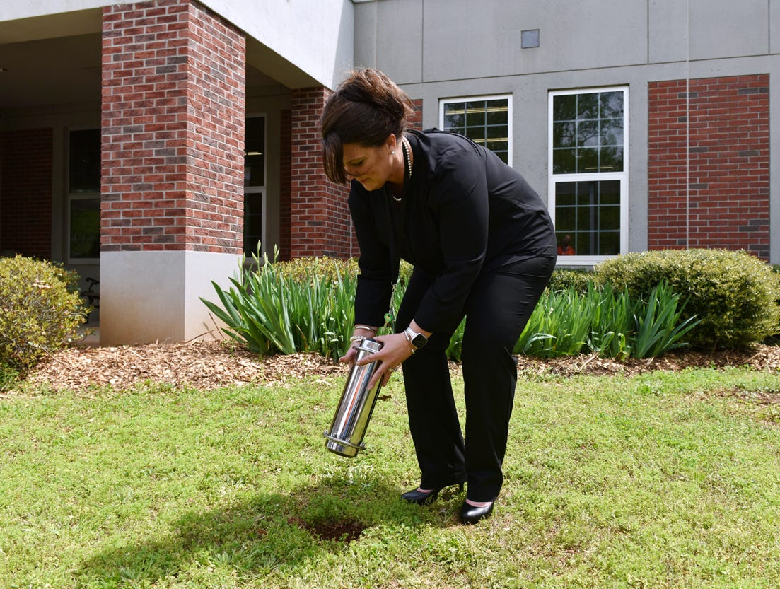 Sue Cleveland Elementary School principal Christie Earley places a time capsule in the ground during the Michelin Challenge Education 10th Anniversary Celebration held at the school on Friday, April 12, 2019.