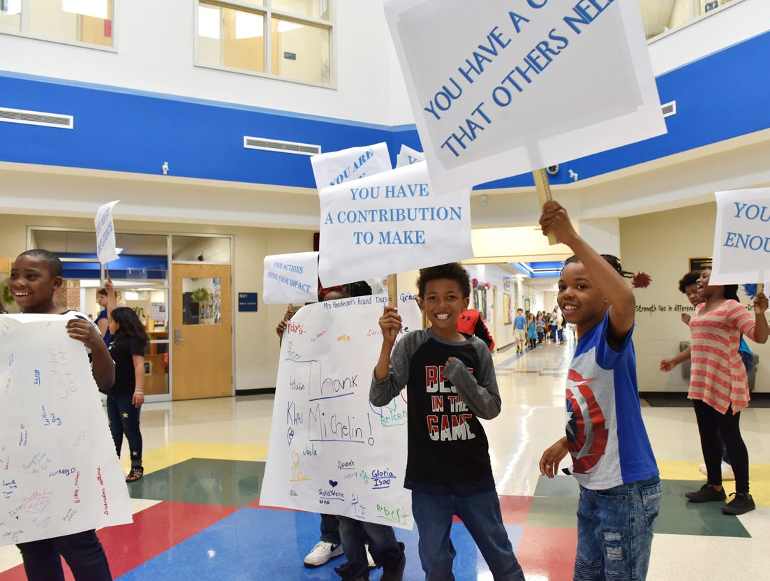 Students at Sue Cleveland Elementary School hold signs welcoming people to the Michelin Challenge Education 10th Anniversary Celebration held at the school on Friday afternoon, April 12, 2019.