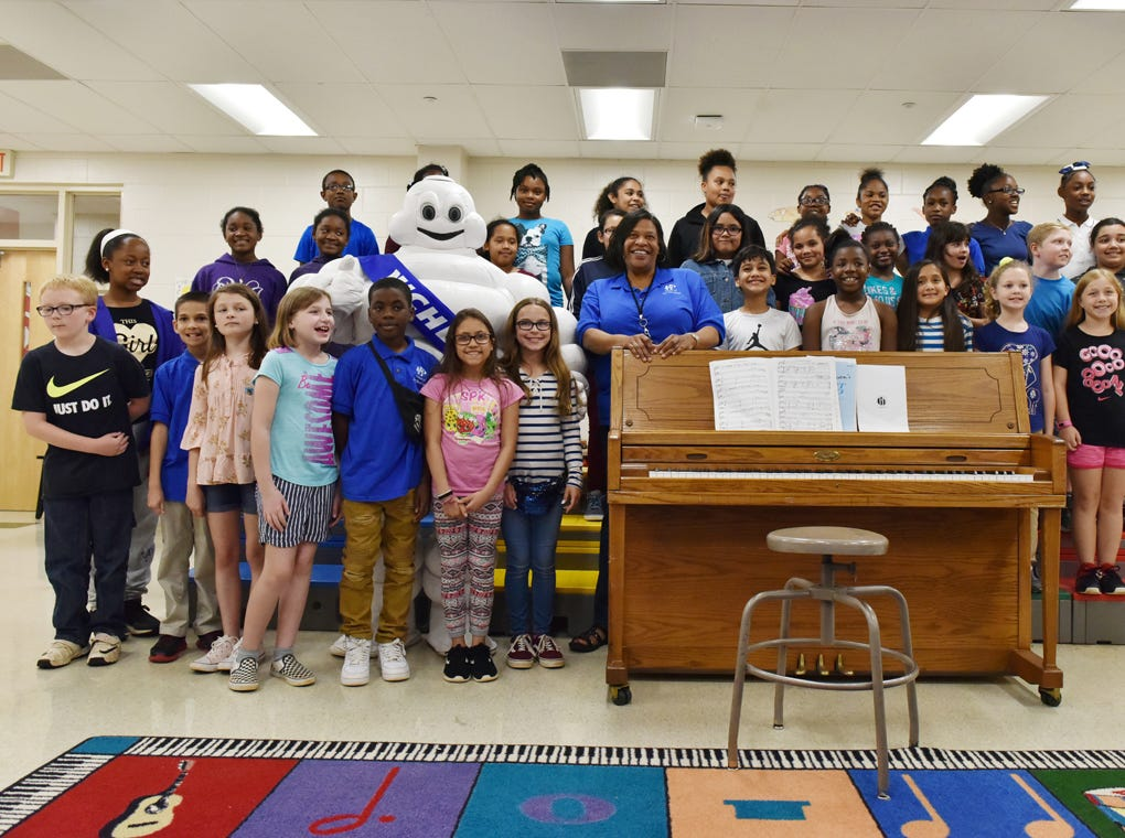 The Sue Cleveland Elementary School choir poses for a photo with the Michelin Man during the Michelin Challenge Education 10th Anniversary Celebration held at the school on Friday, April 12, 2019.