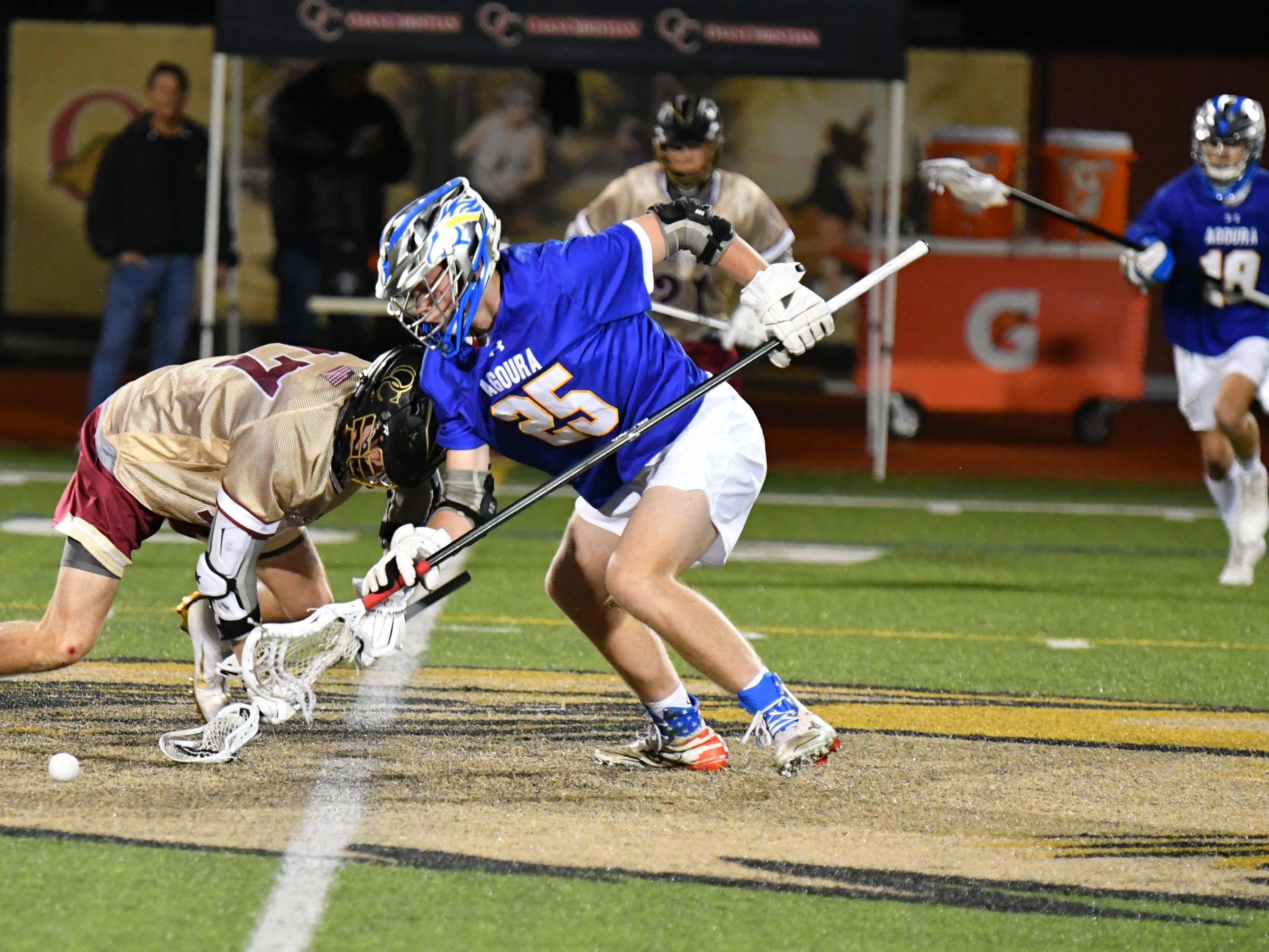 Oaks Christian's Spencer Hill and Agoura's Jaxon Spar battle for a ground ball during the teams' triple-overtime thriller on March 6. Oaks Christian won, 8-7.