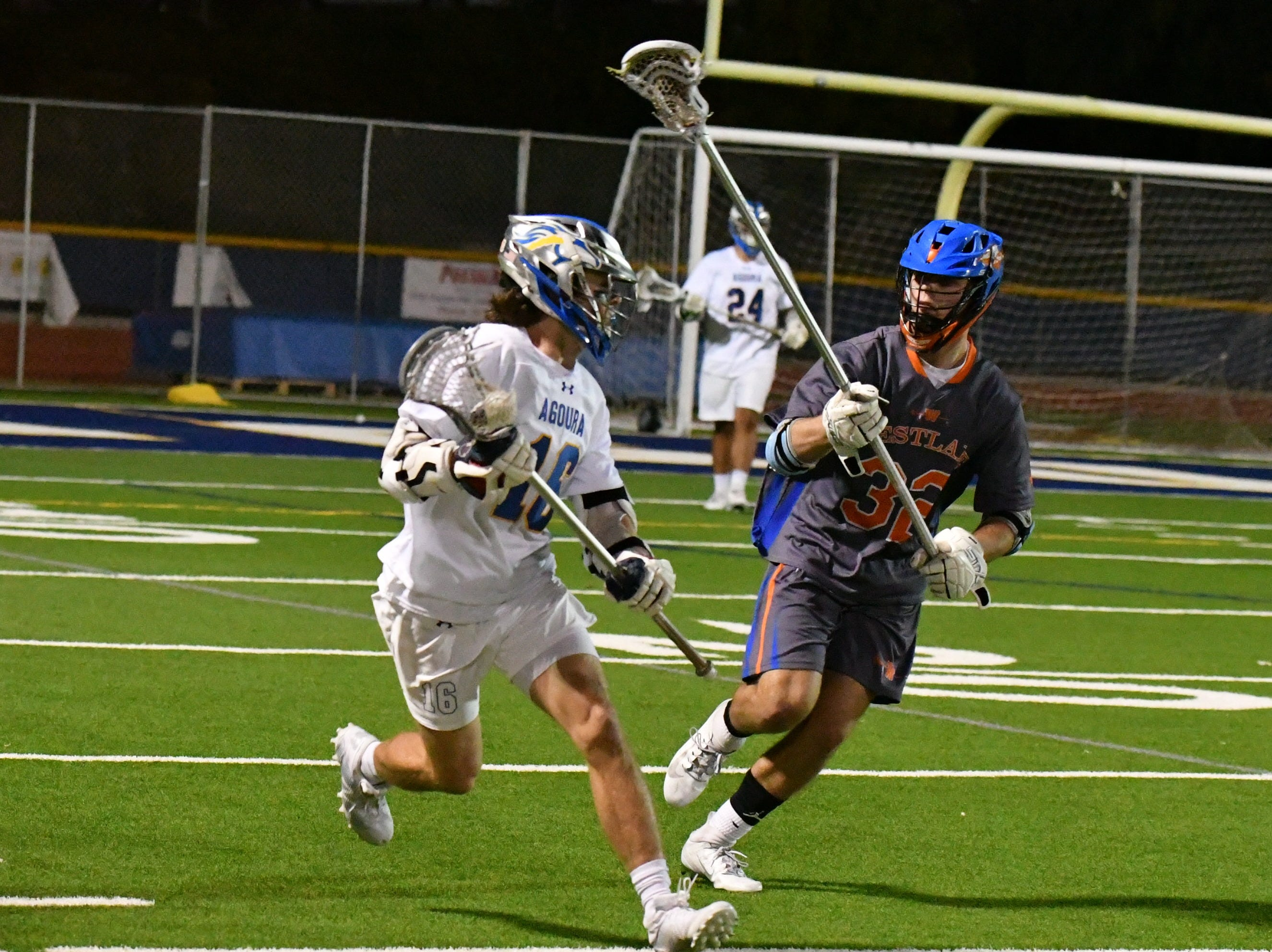 Agoura attackman Dougie McCarthy is chased by Westlake High defender Will Lyman at Agoura High on March 8. The Chargers won, 12-8.