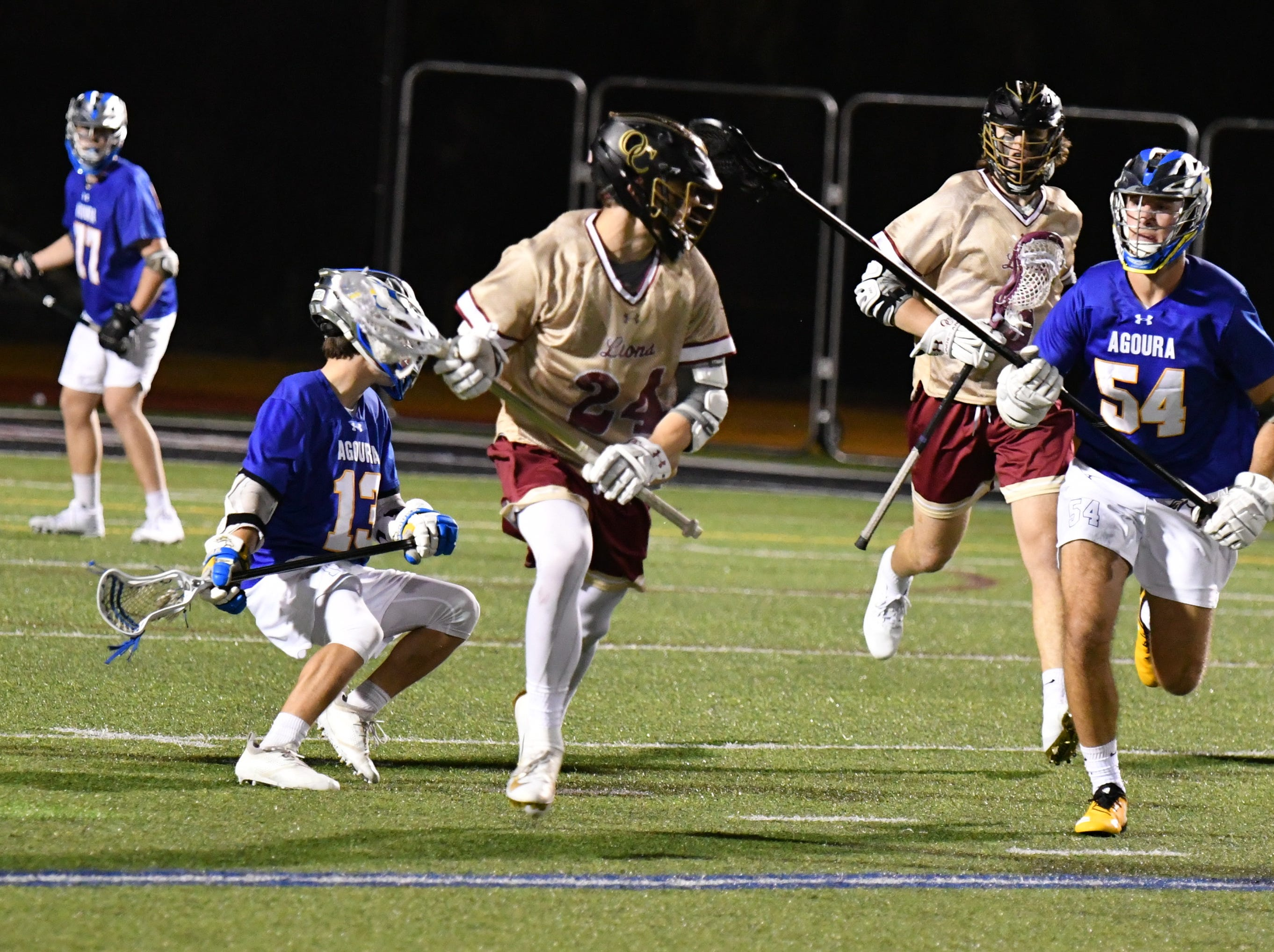 Oaks Christian midfielder Carson Campbell is chased by Agoura defender Nick Tripp during the teams' triple-overtime thriller on March 6. Oaks Christian won, 8-7.