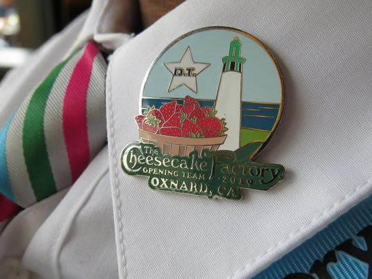 """A Cheesecake Factory team member wears a pin created for the opening of the restaurant's Oxnard location. The """"D.T."""" signifies that the wearer is a designated trainer."""