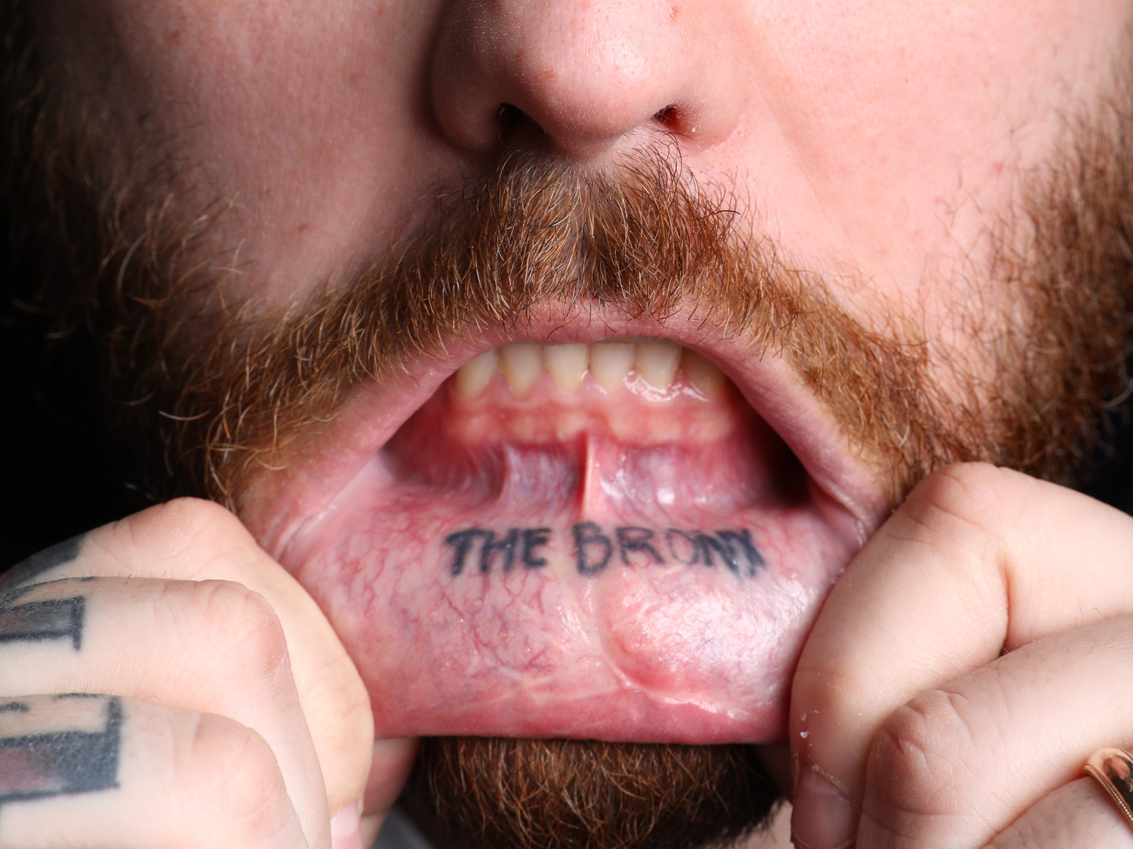 """Christian Petroni, chef and owner of Fortina restaurants, shows his lip tattoo with the words """"The Bronx"""" March 27, 2019 in Yonkers."""