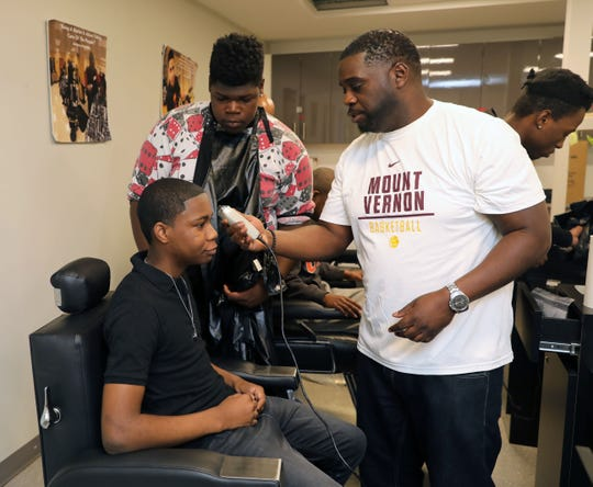 Mount Vernon High School barber students Emmanuel Placide, standing and Joshua Hill, in the chair, watch as instructor Rev Boreland demonstrates a technique during a barber class at the school, April 12, 2019.