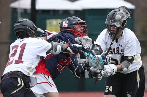 Stepinac's JoJo Warne (22) tries to get between Iona's Chip Cameron (21) and John Schreiber (24) during lacrosse action at Iona Prep in New Rochelle April 11,  2019. Iona won the game 10-6.