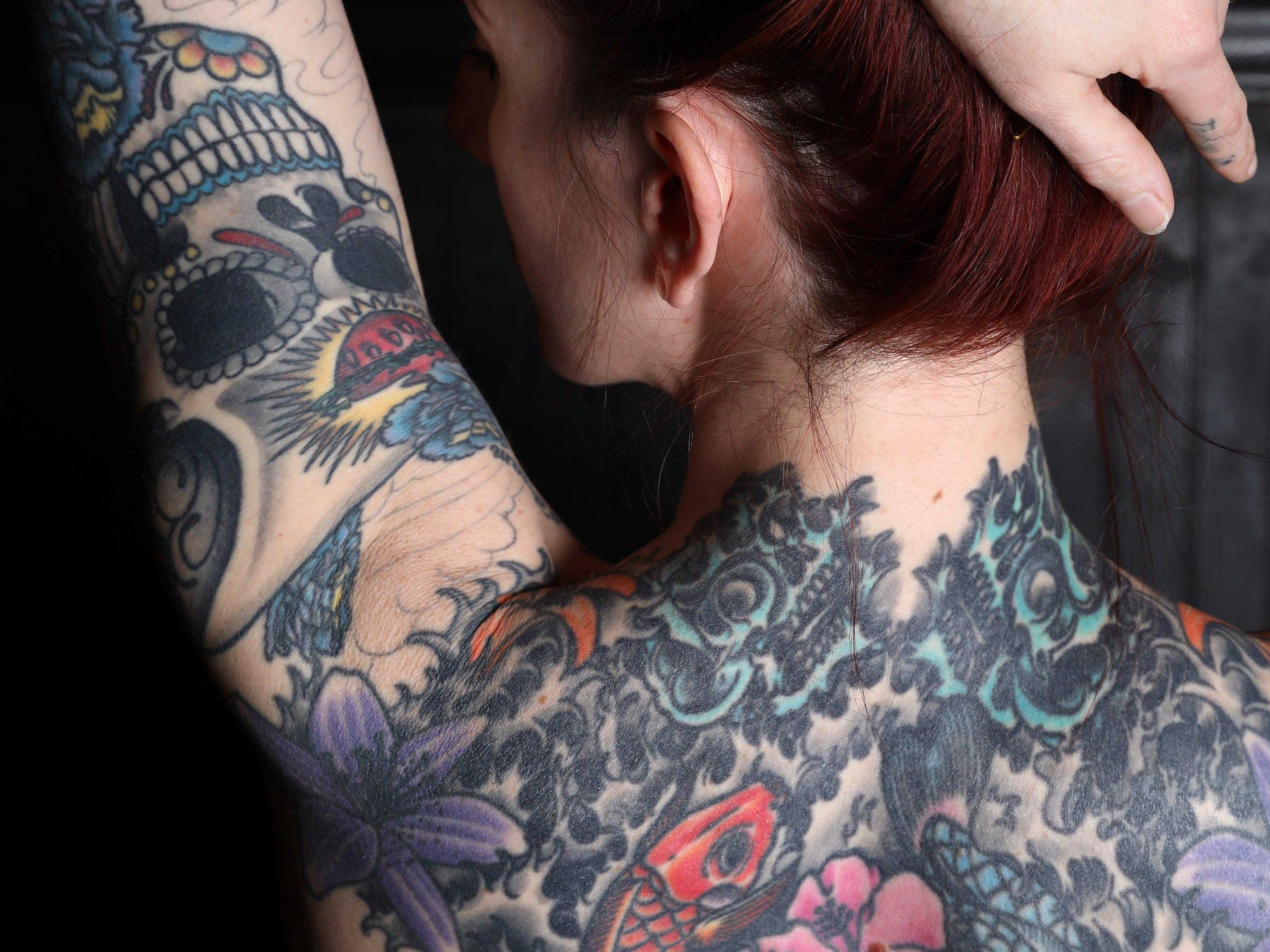Chef Sajin Renae Perino shows her arm and back tattoos; which include sunflowers dedicated to her daughter and two fish, a nod to her and her mother's Pisces zodiac sign, at The Cookery in Dobbs Ferry, where she is the chef de cuisine, March 21, 2019.
