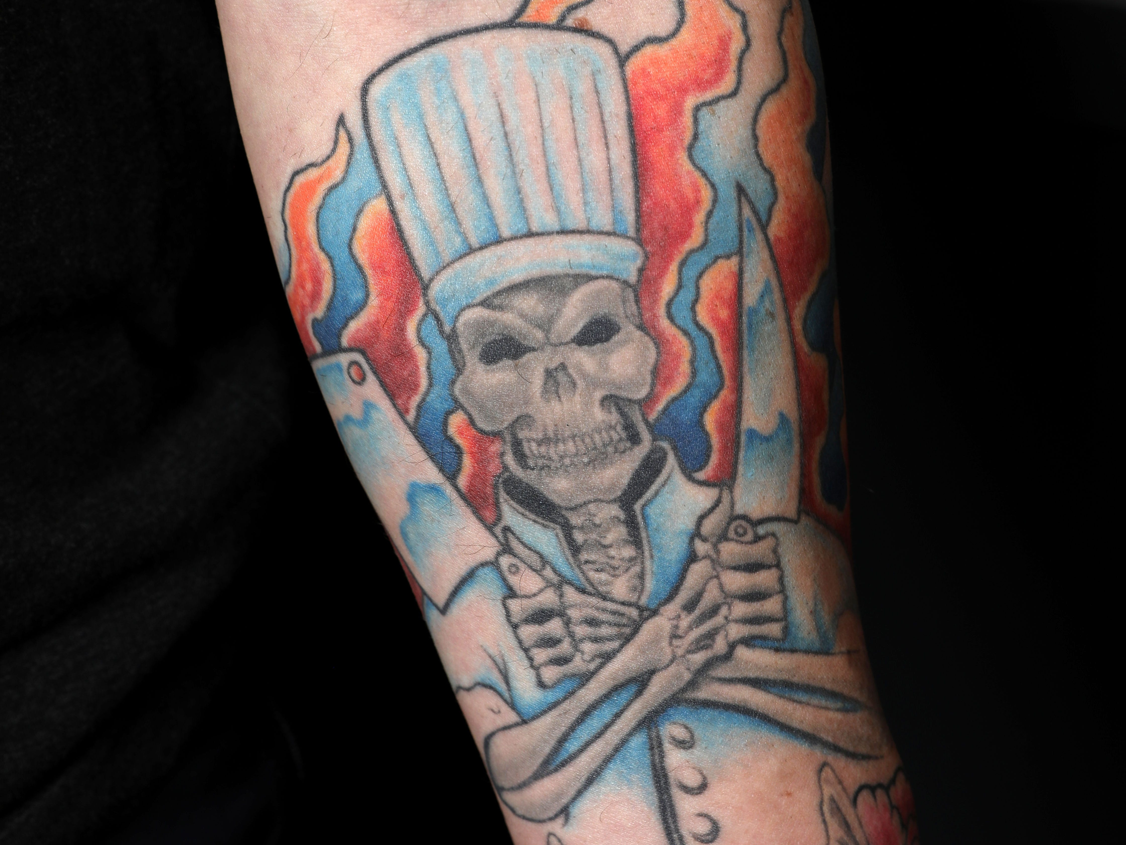 A skeleton chef with knives and fire flames tattoo on chef Matthew Safarowic's arm at The Whitlock in Katonah March 14, 2019.