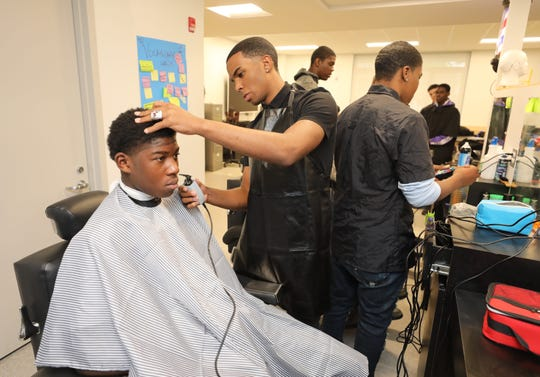 Mount Vernon High School barber student Joel Cooper, center, trims the hair of fellow student Emmanuel Barkor, during a barber class at the school, April 12, 2019.