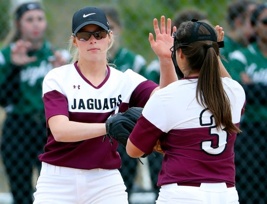 Appoquinimink pitcher Kourtney McNatt (left) slaps hands with third baseman Madeline Olivas after recording an out en route to a perfect game in the Jaguars' 3-0 home win against Mount Pleasant last Thursday.