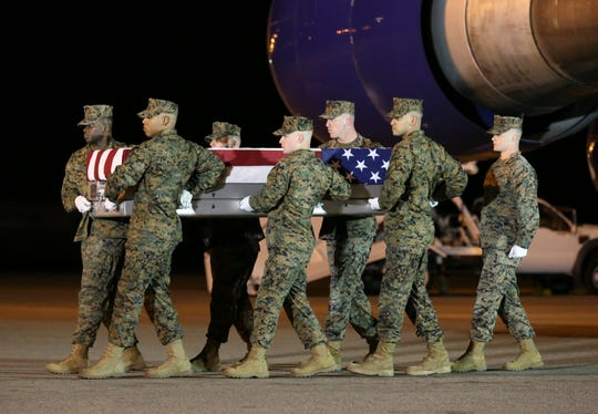 The remains of Marine Staff Sgt. Christopher A. Slutman are transferred from a plane to the mortuary at Dover Air Force Base in a solemn process Thursday evening.