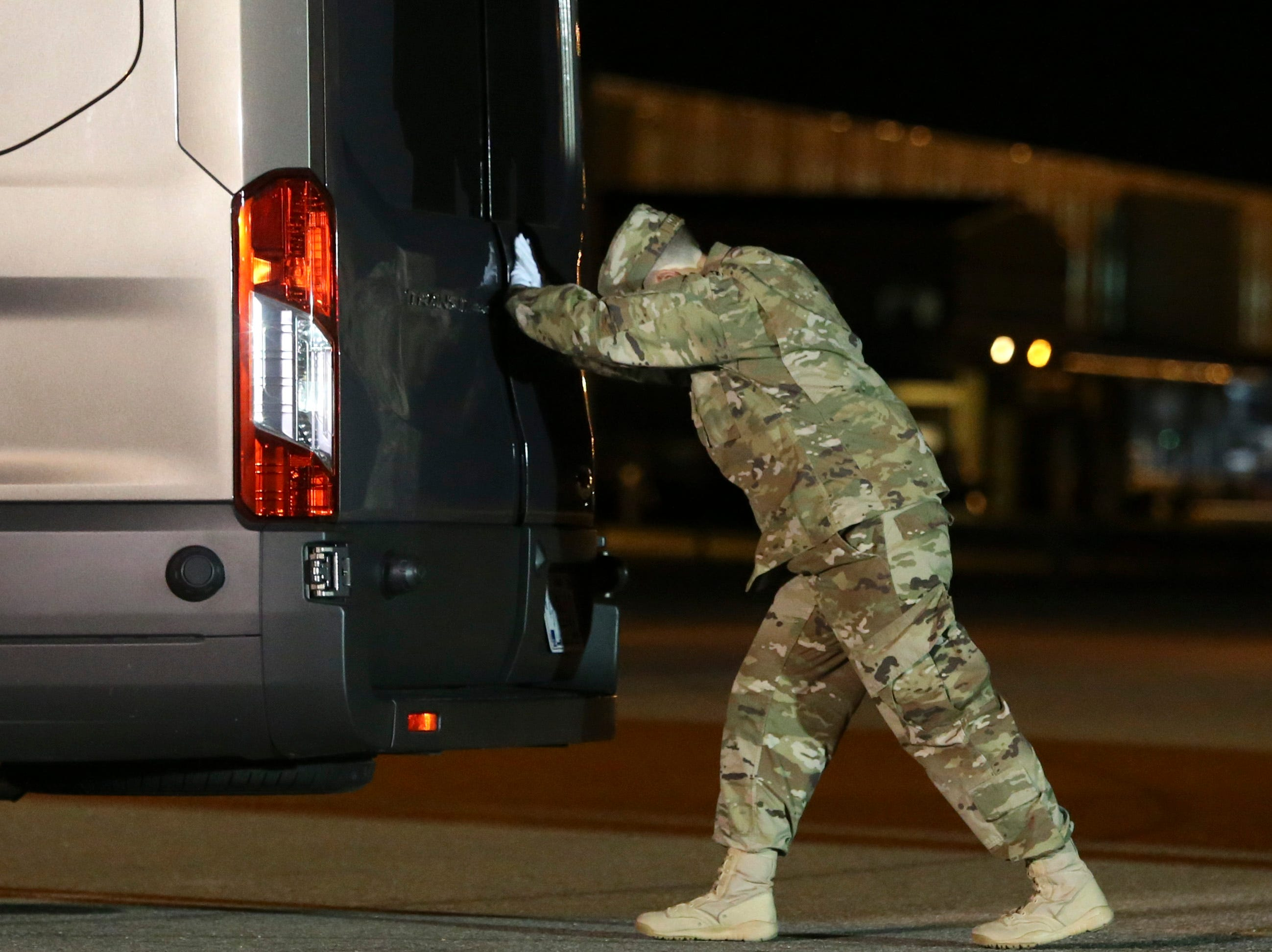 Senior Airman Electa Hazenstab secures the doors to a van that will carry the remains of Marine Staff Sgt. Christopher A. Slutman from a plane to the mortuary at Dover Air Force Base in a solemn process Thursday evening.