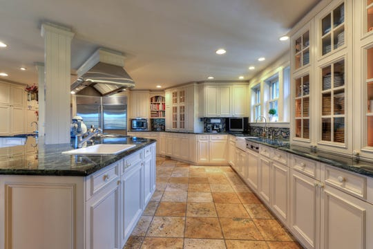 The  oversized gourmet kitchen including a six-burner gas range, two ovens, Sub-Zero refrigerators, ice maker, built-in microwave, marble countertops, travertine tile floors, a wet bar area and a butler's pantry.