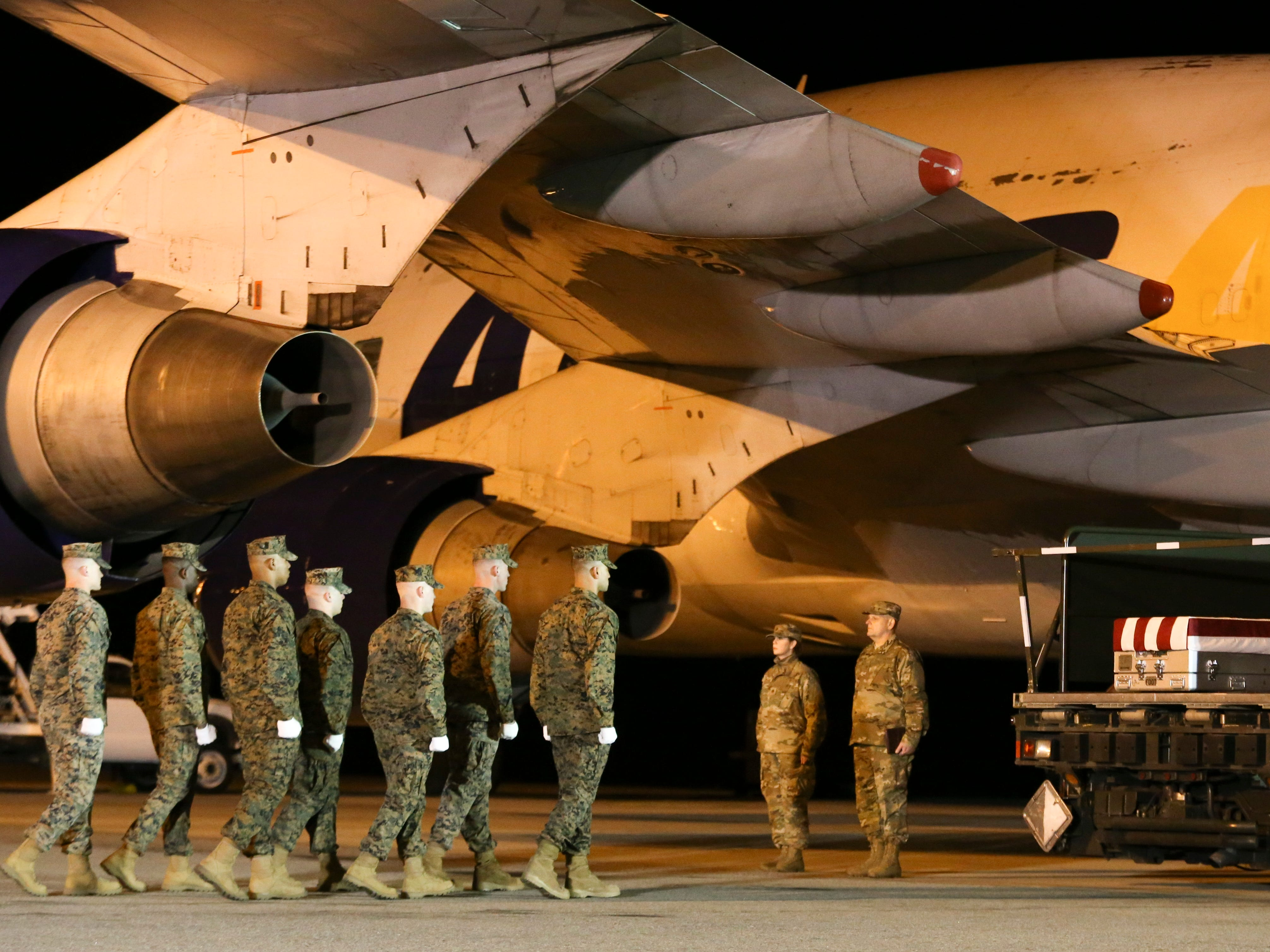 Marines move to transfer the remains of Marine Staff Sgt. Christopher A. Slutman at Dover Air Force Base in a solemn process Thursday evening.