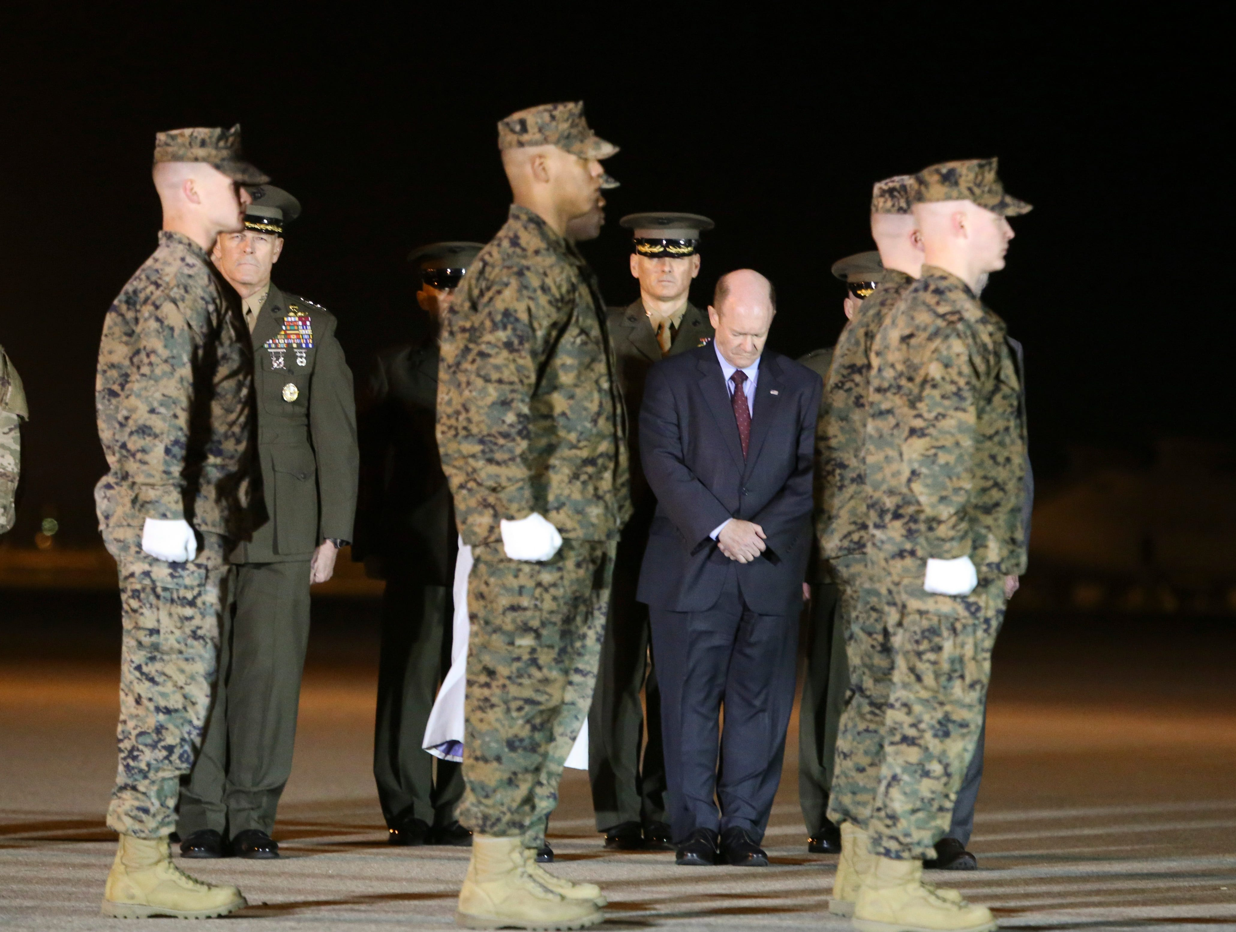 U.S. Senator Chris Coons (wearing suit), in attendance with the rest of the Delaware congressional delegation, bows in prayer as the remains of Staff Sgt. Christopher Slutman are transferred at Dover Air Force Base in a solemn process Thursday evening.