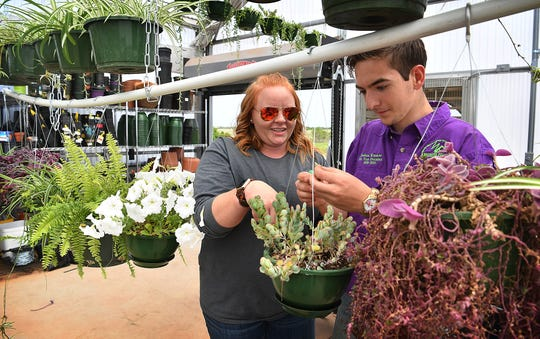 Amber West, agriculture teacher at the Career Education Center, works with junior Joshua Winsauer as they prepare plants for the 2nd annual Plant Sale in the campus greenhouse. The sale continues Saturday 9 a.m to 2 p.m.