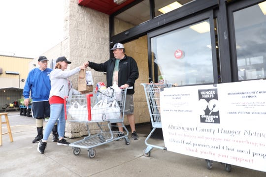 Riesbeck's customer Jim Neff hands Jamie Trout of Eastside Community Ministry a donation Friday during the Operation Feed Store Collection Day. Volunteers were collecting food at WalMart North, WalMart South, and Riesbeck's dowtown location. All food collected will benefit the 15 local food pantries, one baby pantry, and four hot meal programs of the Muskingum County Hunger Network.