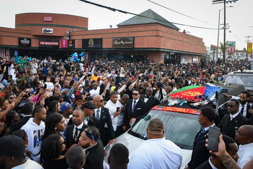 Hundreds of supporters cheer and watch as Nipsey Hussle's casket passes The Marathon Store on the corner of Crenshaw and Slauson on April 11, 2019.