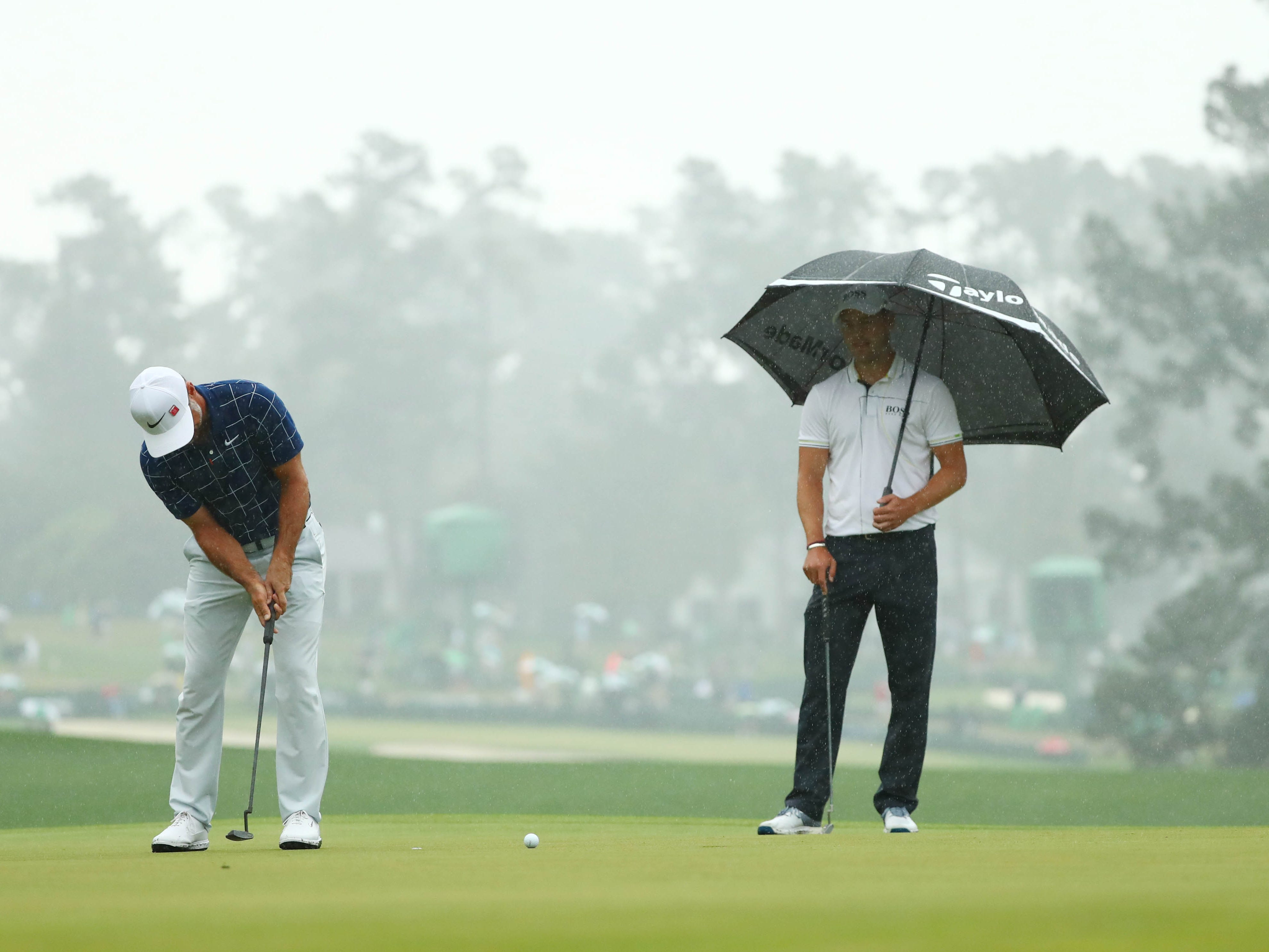 Trevor Immelman putts on the first green as Martin Kaymer stands under an umbrella during the second round of the Masters.