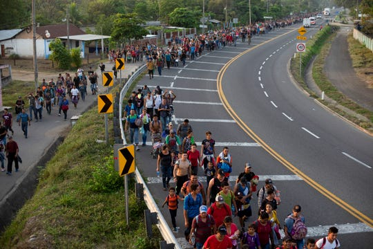 Central American migrants, part of the caravan hoping to reach the U.S. border, walk on the shoulder of a road in Frontera Hidalgo, Mexico, Friday, April 12, 2019. The group pushed past police guarding the bridge and joined a larger group of about 2,000 migrants who are walking toward Tapachula, the latest caravan to enter Mexico.